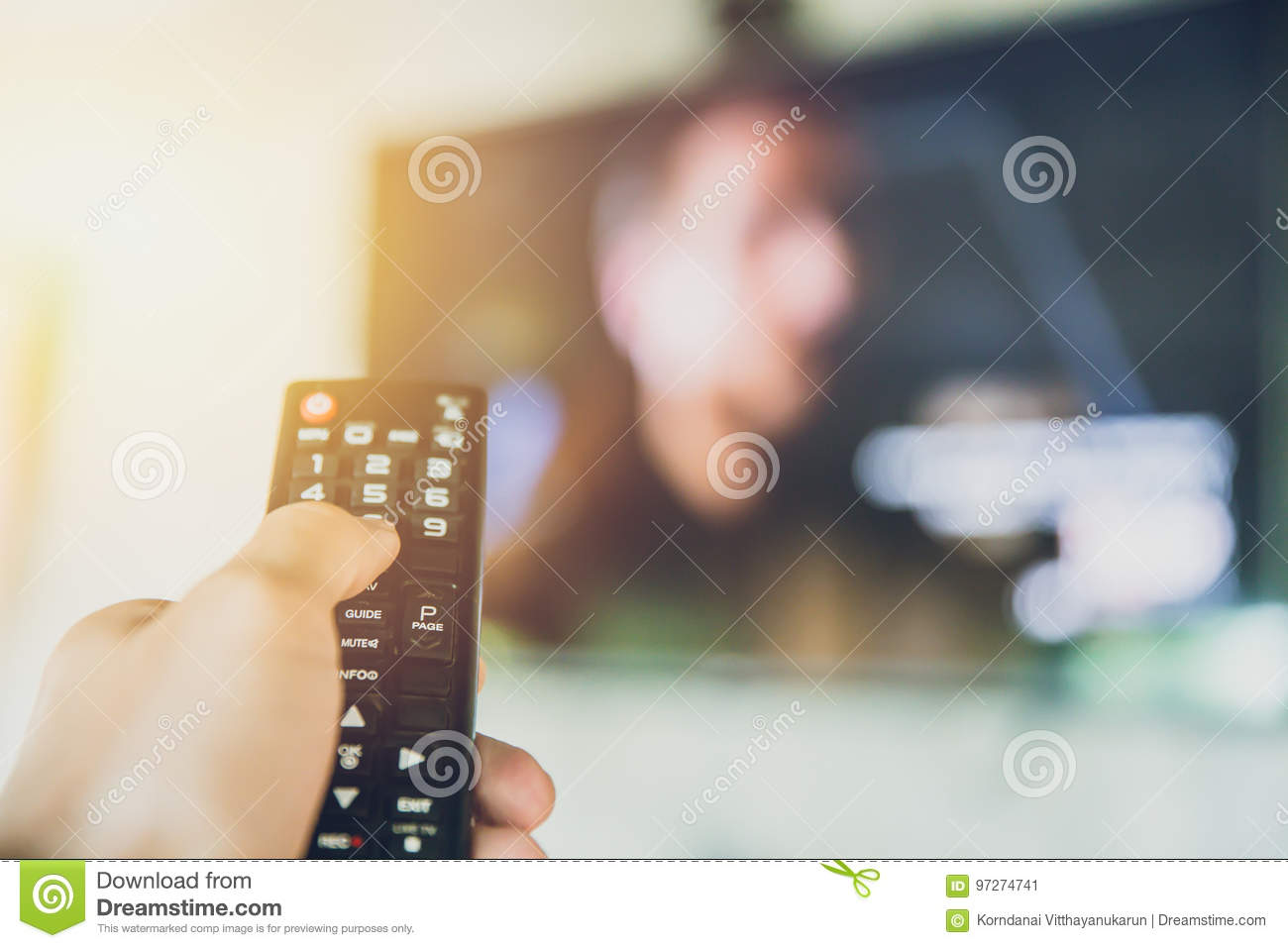 Home entertainment. hand hold Smart TV remote control with a television blur background