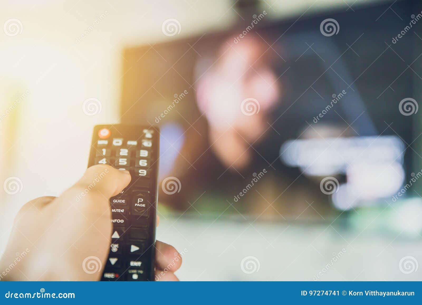 Home Entertainment prise Smart TV de main à télécommande avec un fond de tache floue de télévision