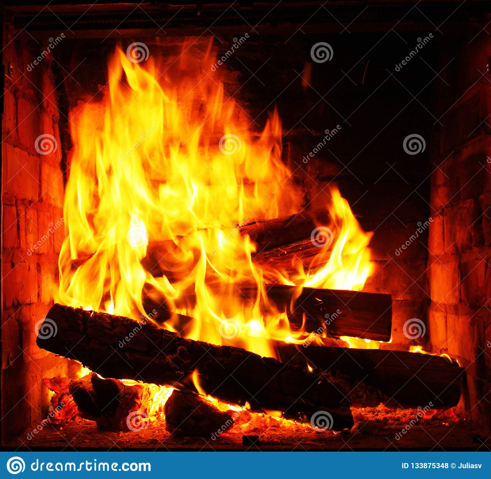 Home fireplace with beautiful orange fire and wood fire close-up