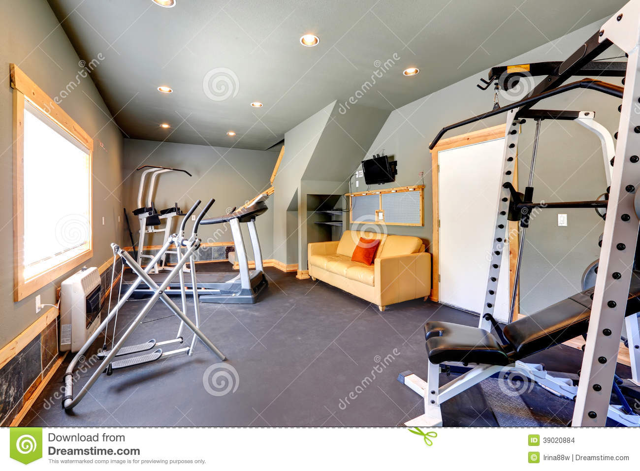 Home gym with yellow couch and tv stock photo image of
