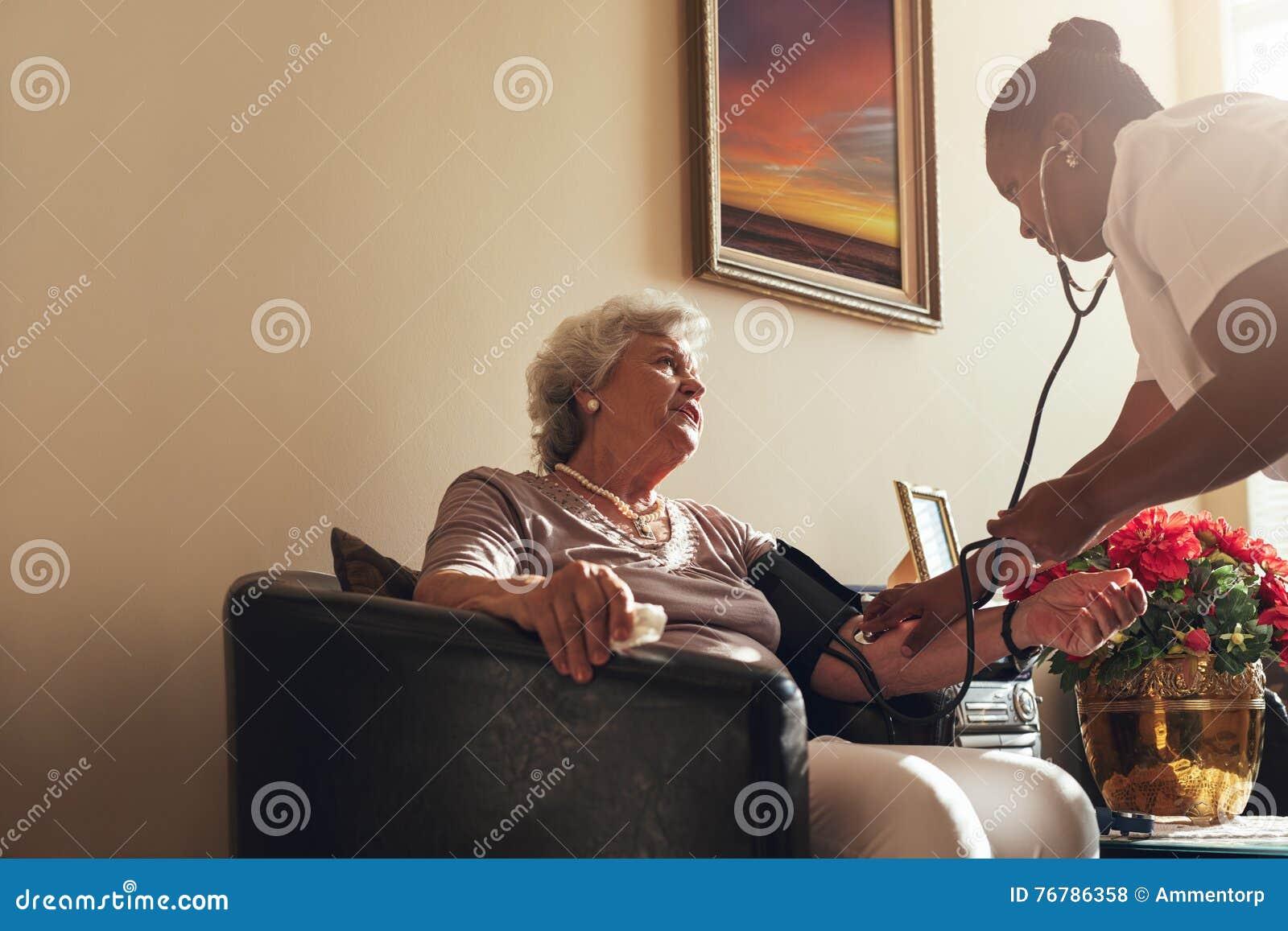 Home healthcare nurse checking blood pressure of senior woman