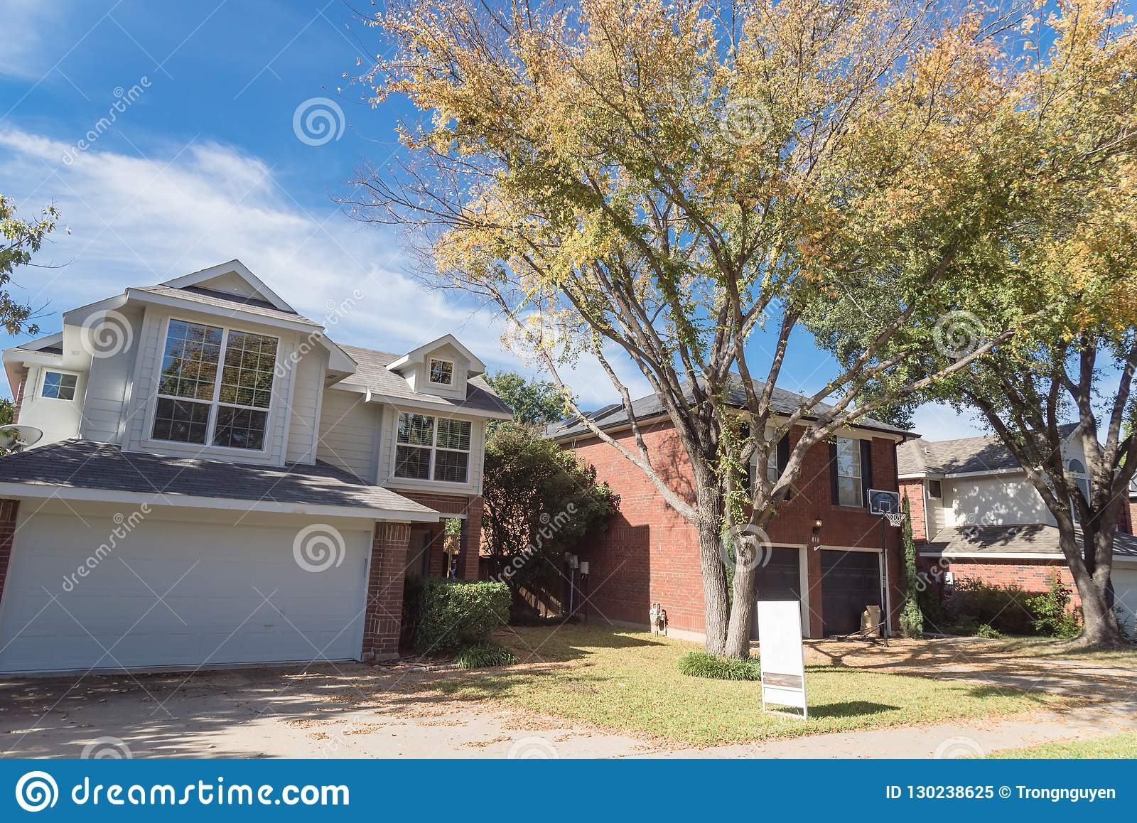 Home With House For Sale Yard Sign And Colorful Fall Foliage In
