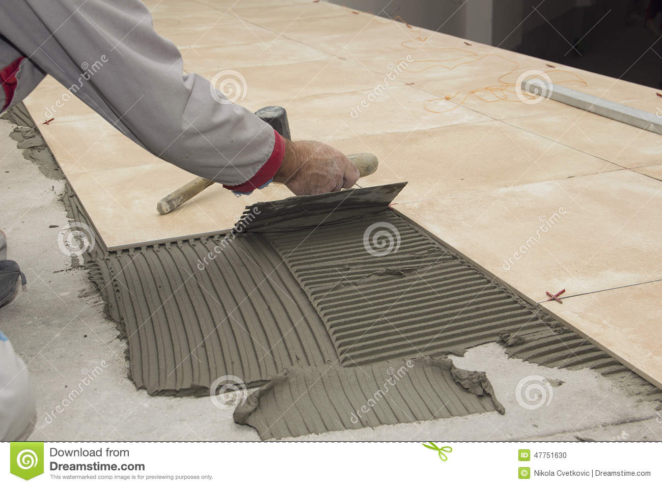 home-improvement-renovation-construction-worker-tiler-tiling-ceramic-tile-floor-adhesive-trowel-mortar-close-up-47751630.jpg