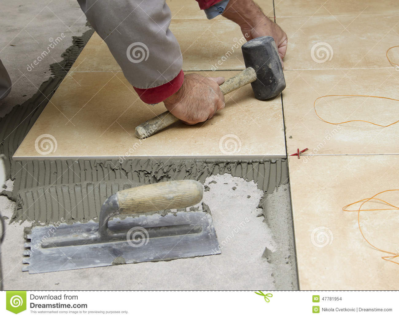 Home improvement renovation construction worker tiler is tiling home improvement renovation construction worker tiler is tiling ceramic tile floor adhesive trowel with mortar dailygadgetfo Image collections