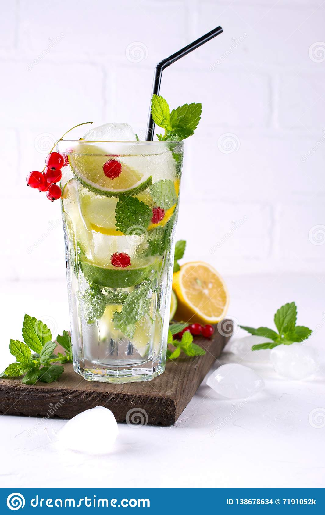 Home made mojito cocktail with lemon, lime, mint leaves, with ice and red currant
