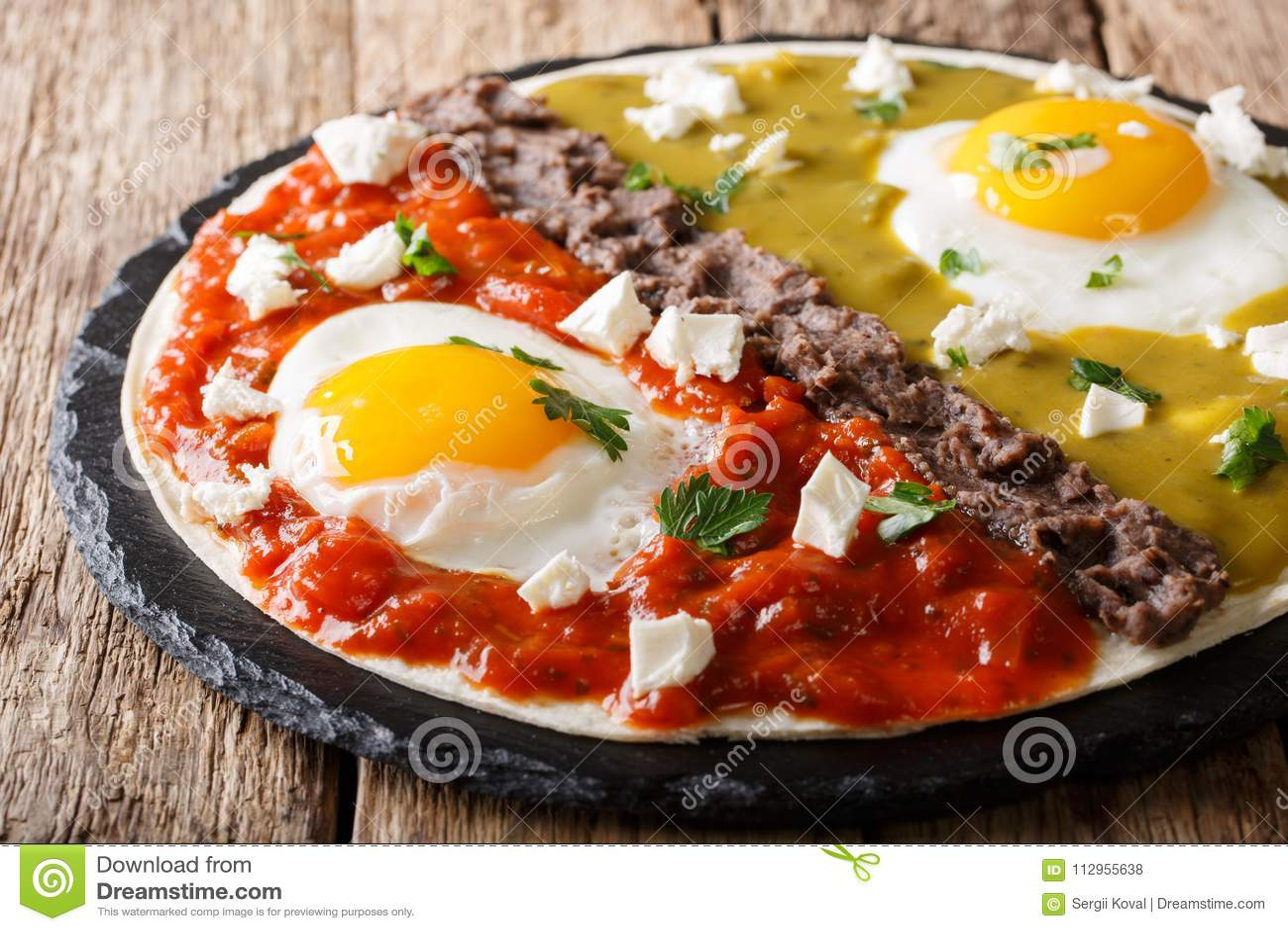 Home Mexican food: huevos divorciados with Frijoles refritos, two sauces roja and verde and cheese Queso Fresco on tortilla macro