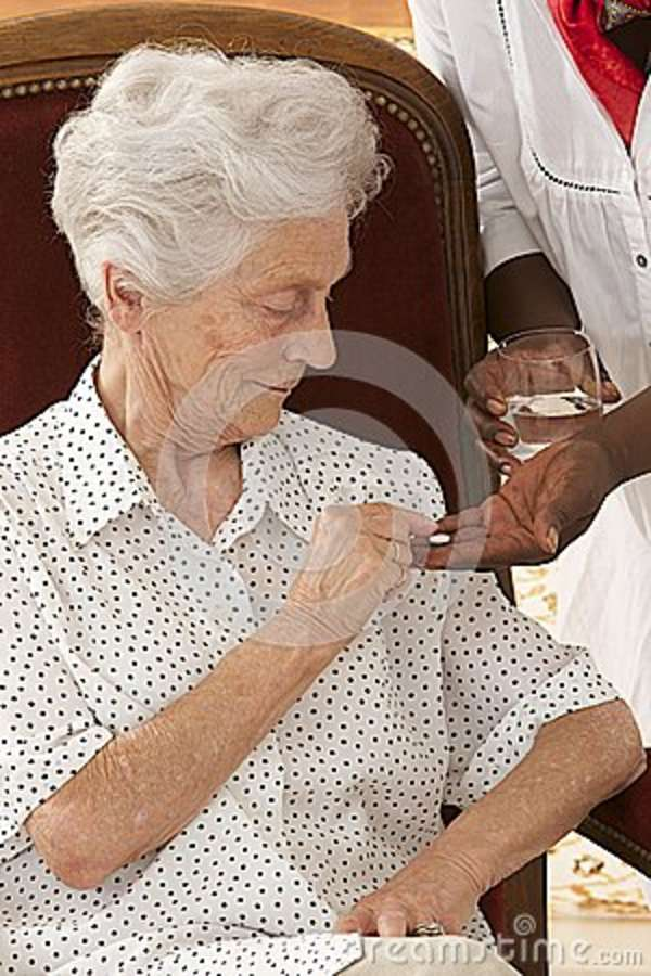 Home nurse giving elderly woman vitamin pills at home