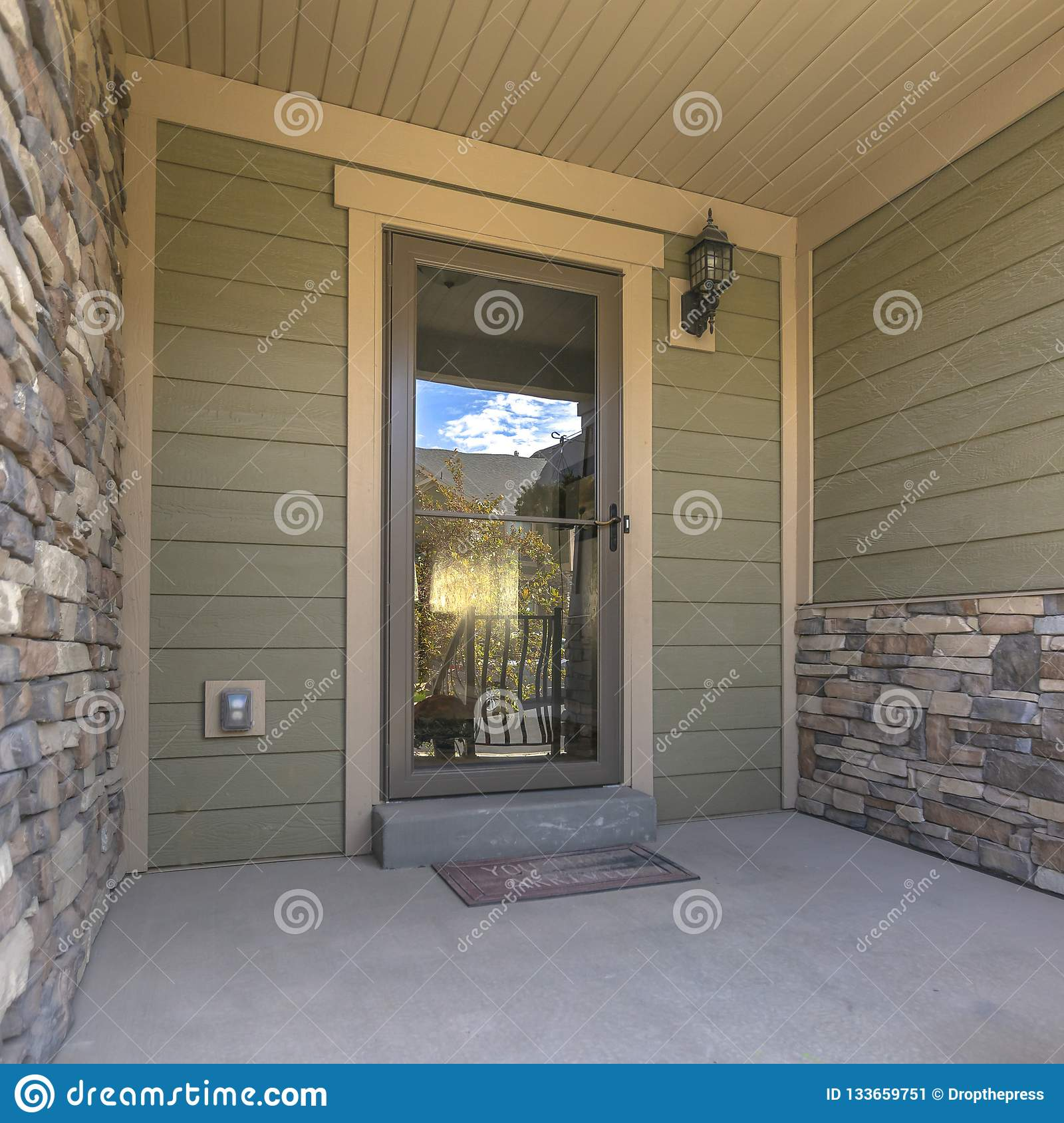 home porch reflective glass front door entryway reflecting stairs trees sunny sky has wooden brick exterior wall 133659751