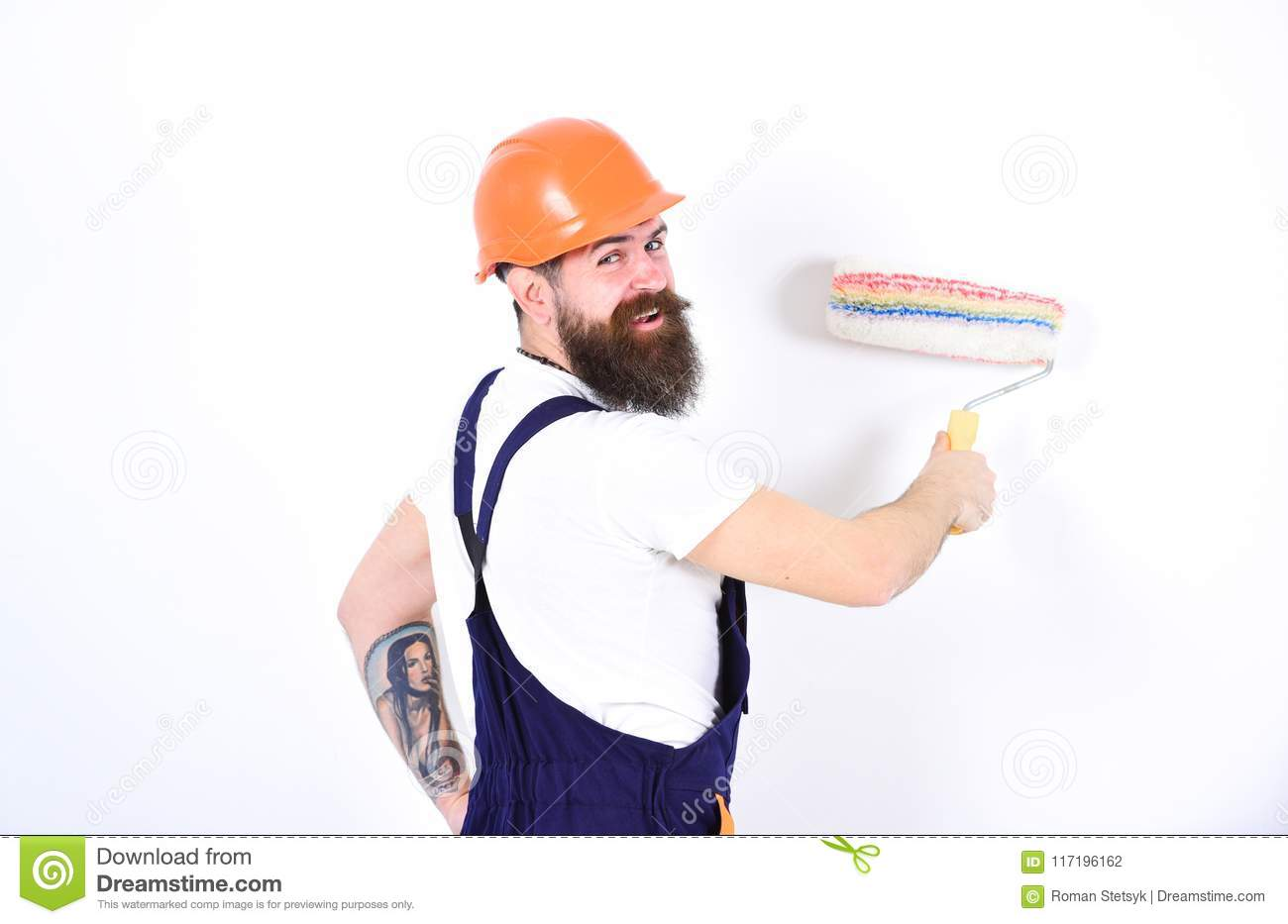 Home redecoration concept. Turn back smiling builder painting wall with paint roller. Isolated man in orange helmet and