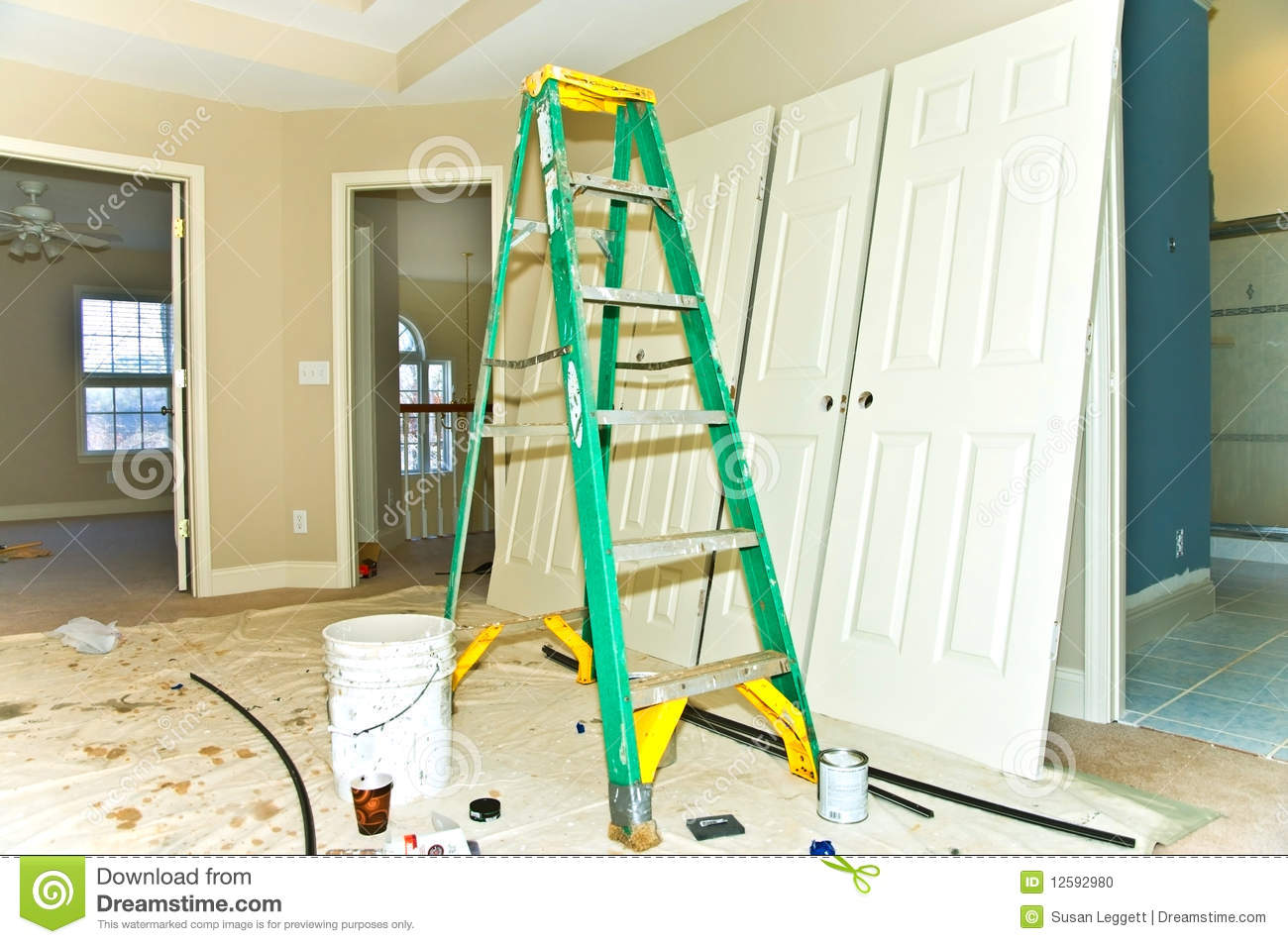 remodeling job being done on a house, painting supplies, a ladder ...