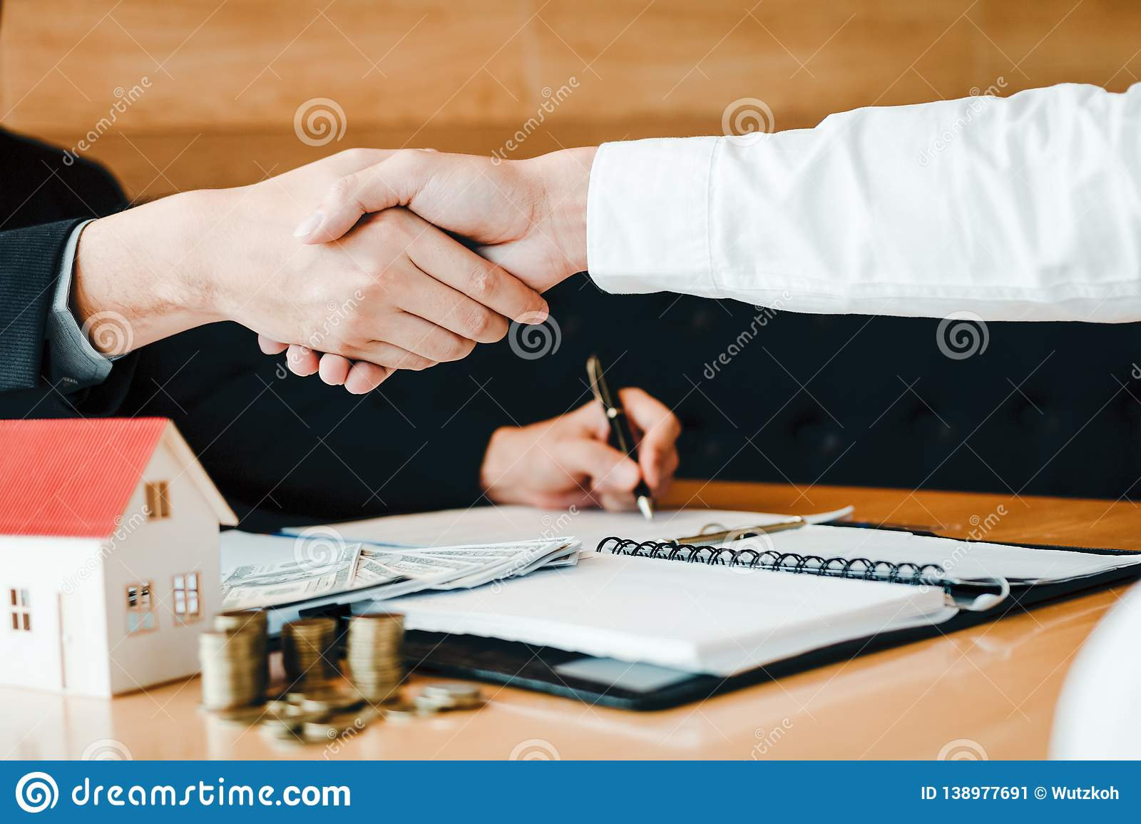 Home sales agents and buyers work on signing new homes and shaking hands