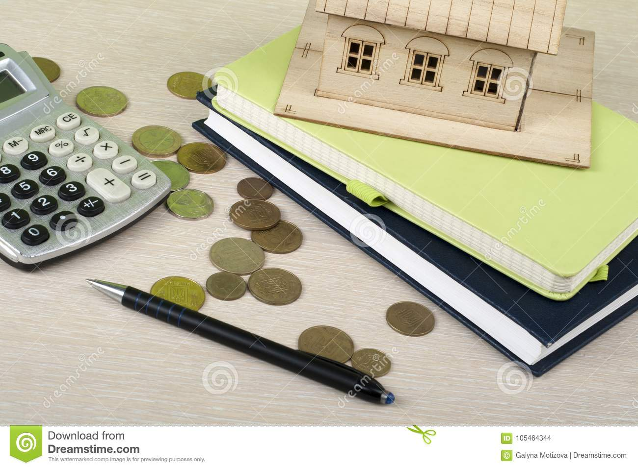 Home savings, budget concept. Model house, notepad, calculator,pen and coins on wooden office desk table.