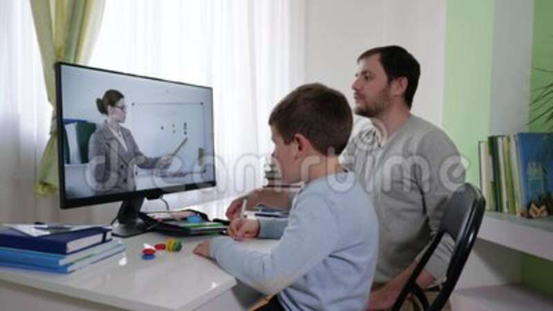 Home schooling, parent helps his son learn lessons during an online lesson with a teacher, a father explains homework to