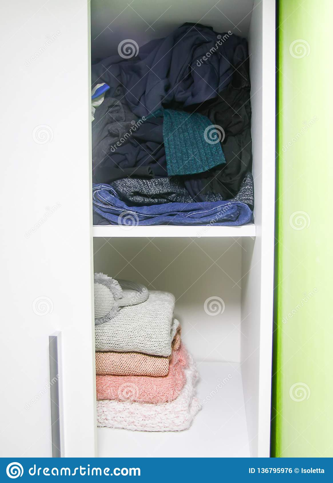 Home wardrobe with clothes. Small space organization. The contrast of order and disorder