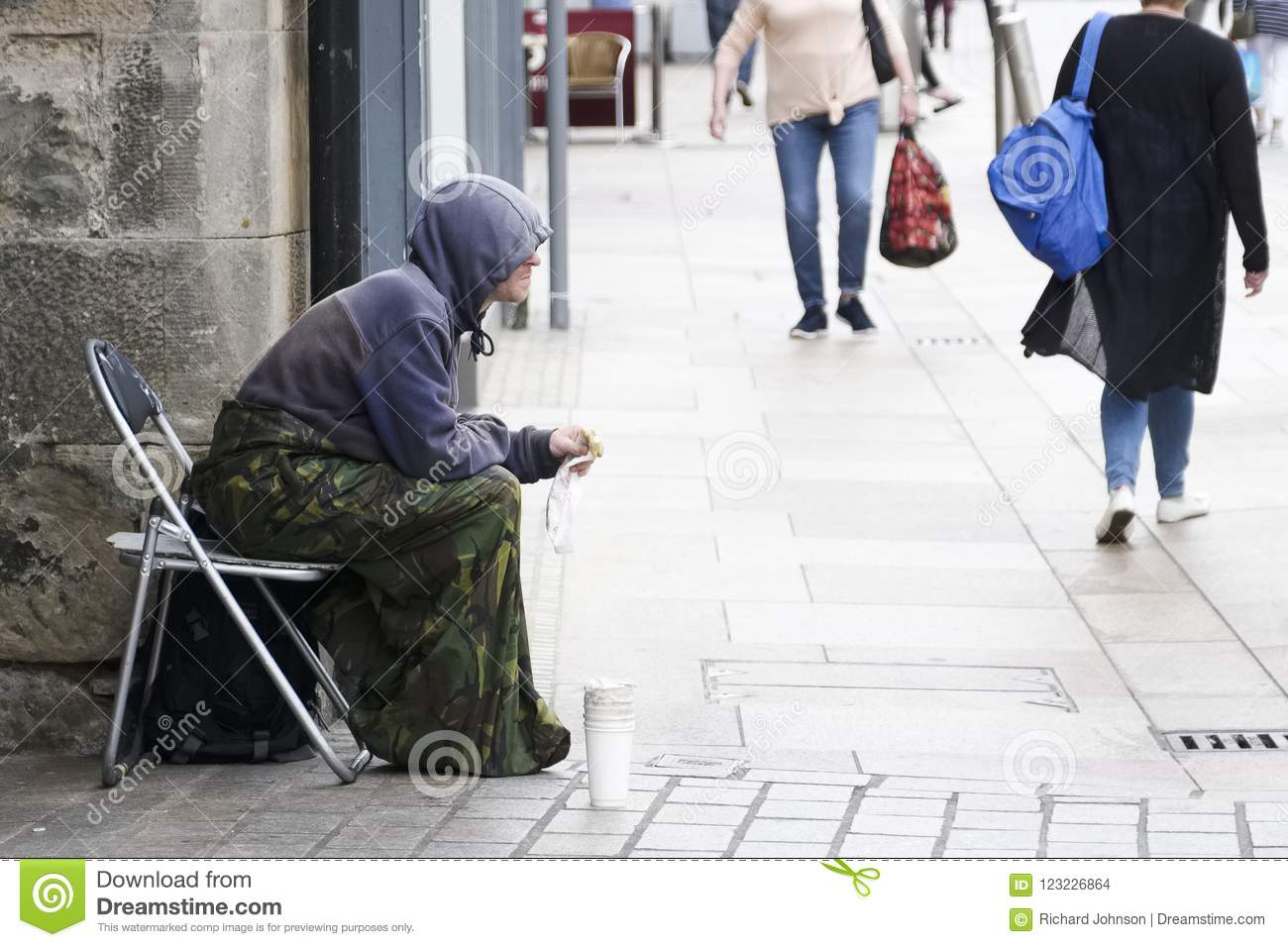 Homeless beggar sat on busy street wearing a hoodie with cup for change in the UK with shoppers in the background