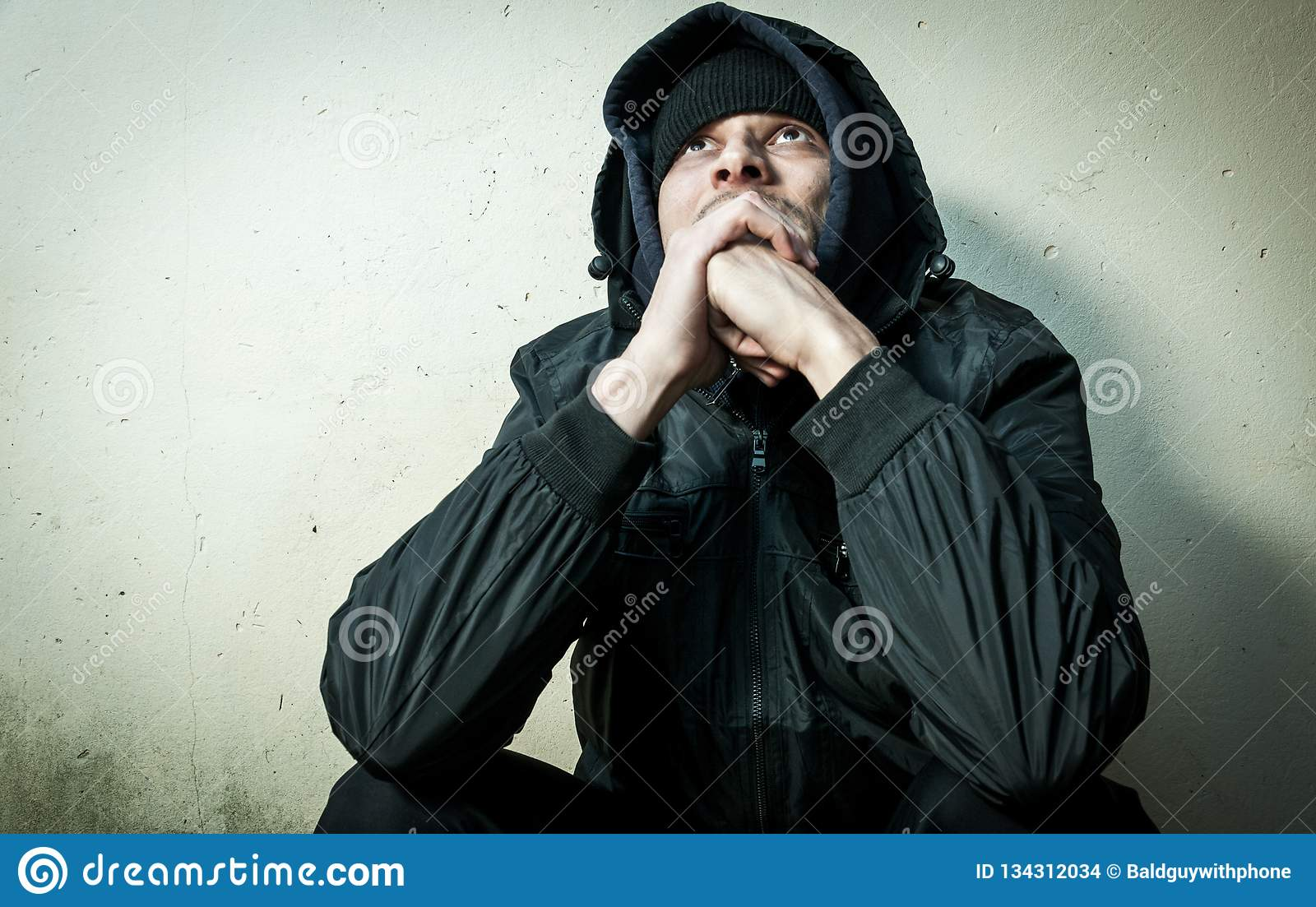 Homeless man drug and alcohol addict sitting alone and depressed on the street in winter clothes feeling anxious cold and lonely,