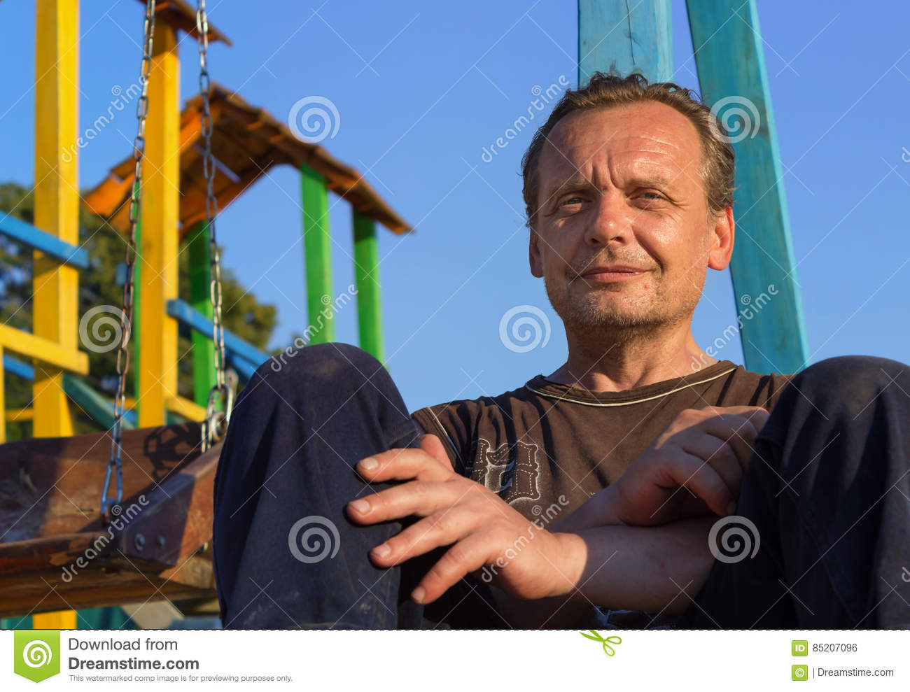 Homeless Man. Poor people in the children`s Playground at sunse