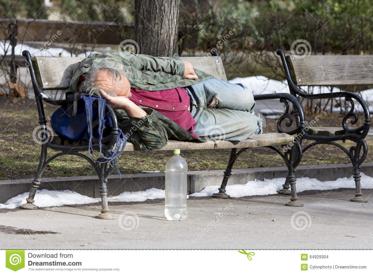 homeless man sleeping on a bench editorial stock image