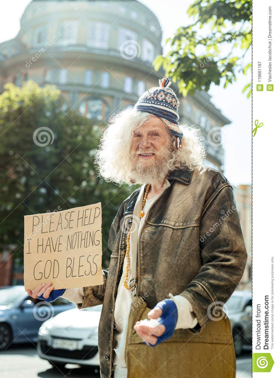 d6c370e5abe Homeless starving man wearing old brown leather jacket holding sign asking  for help
