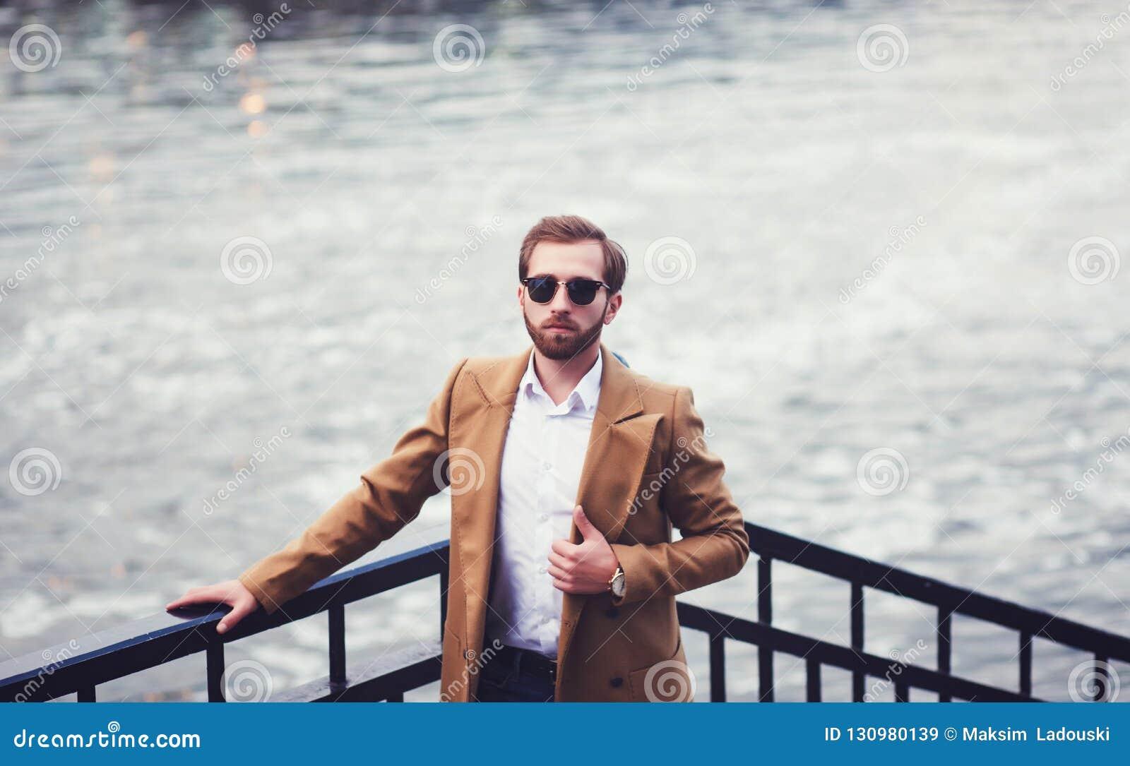 Homem à moda com uma barba em um revestimento