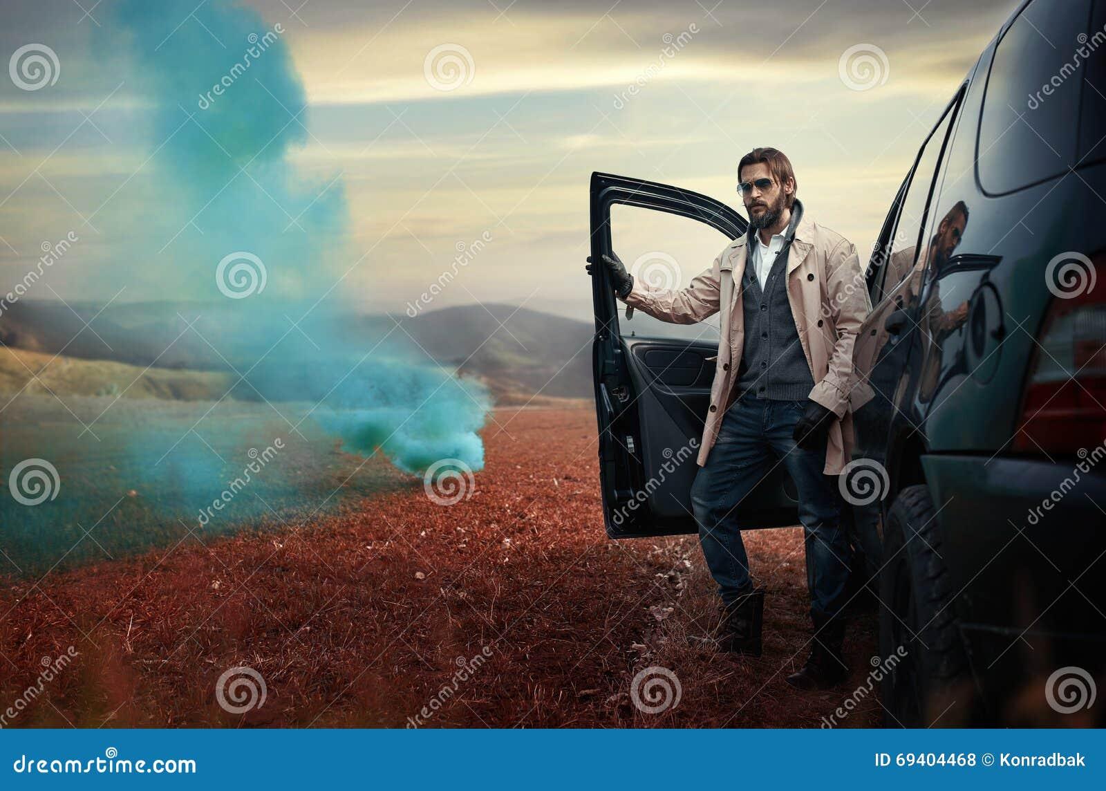 Homem à moda considerável na estrada ao lado de seu carro
