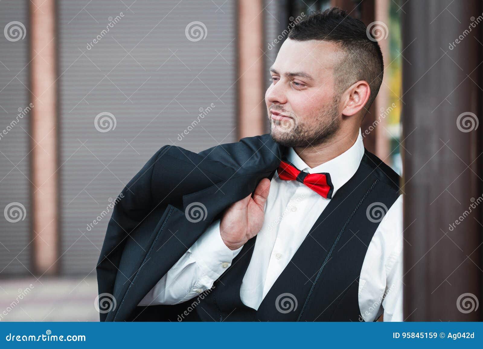 Homem à moda novo em um terno Retrato do noivo O noivo está guardando seu revestimento em seu ombro, vista lateral