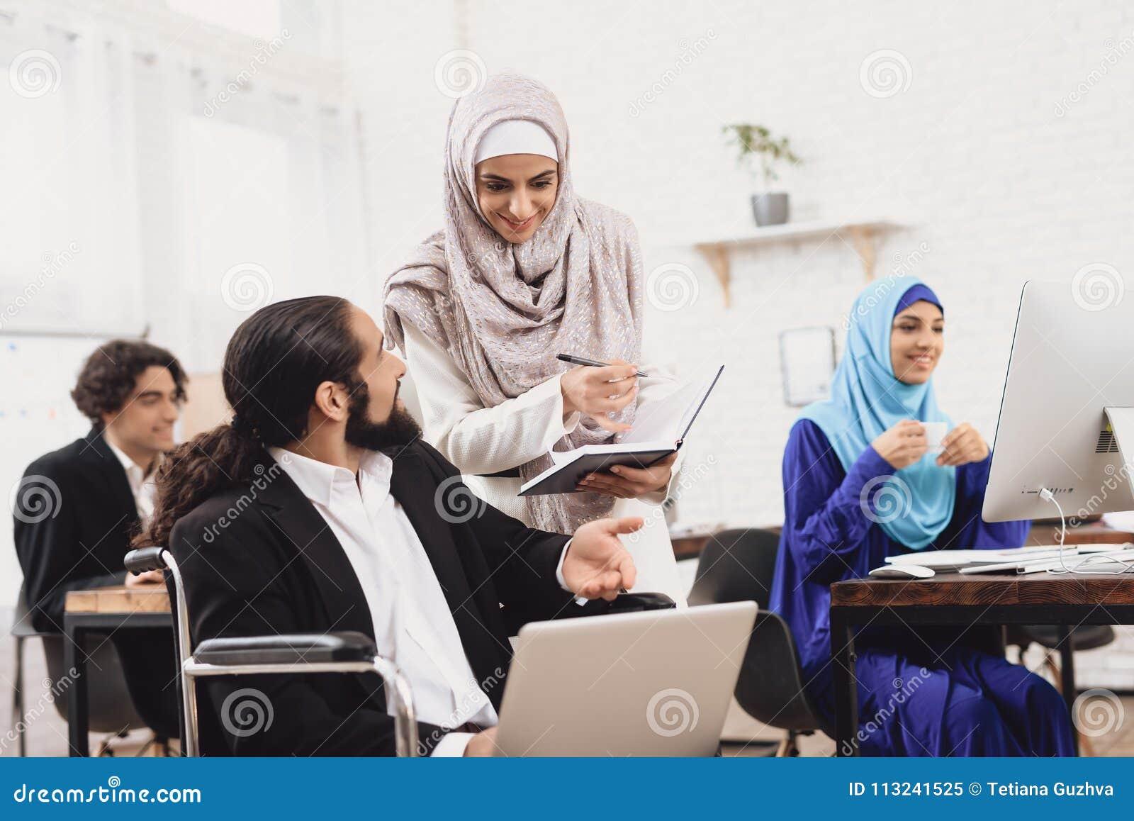 Homem árabe deficiente na cadeira de rodas que trabalha no escritório O homem está falando ao colega de trabalho fêmea