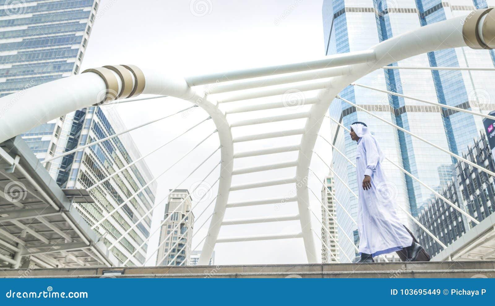 Homem árabe do saudita do viajante do negócio que leva uma mala de viagem e uma caminhada dentro