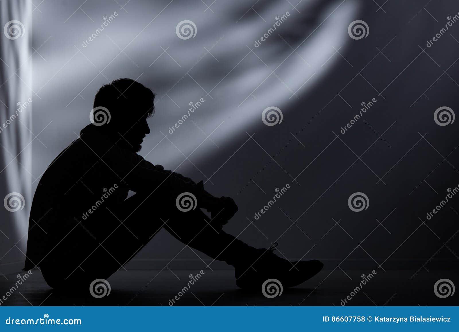 Homem abandonado na sala escura
