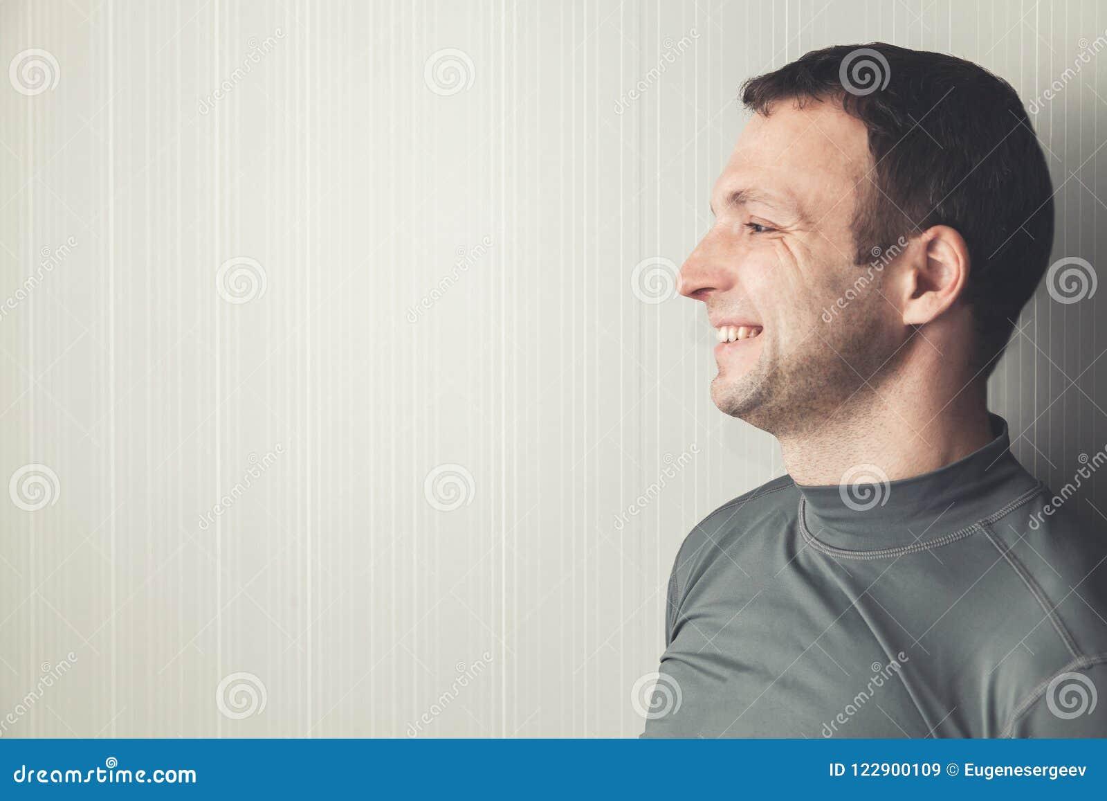 Homem adulto novo de sorriso no sportswear cinzento