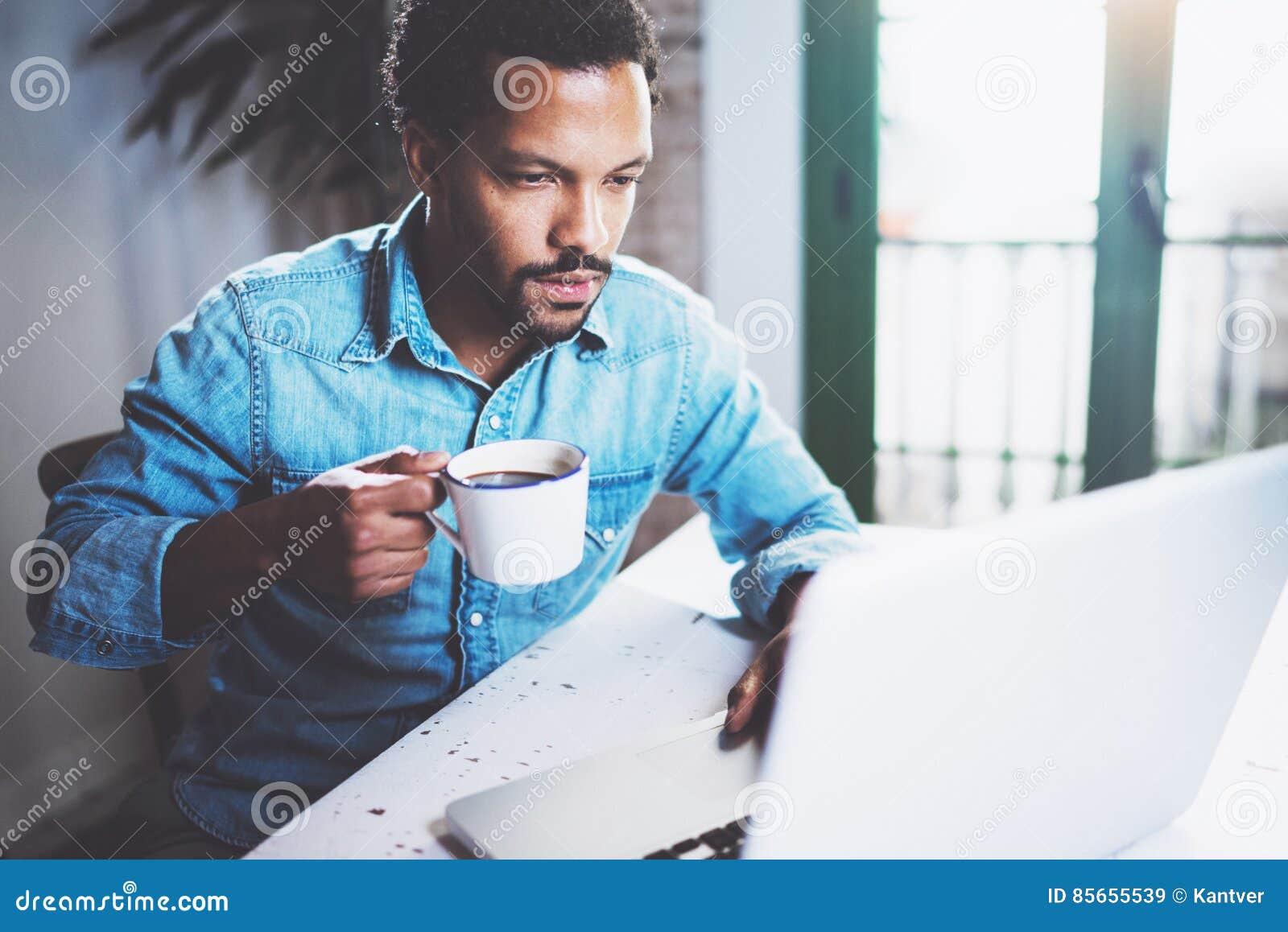 Homem africano farpado pensativo que usa a casa do portátil quando café preto de copo bebendo na tabela de madeira Conceito dos j
