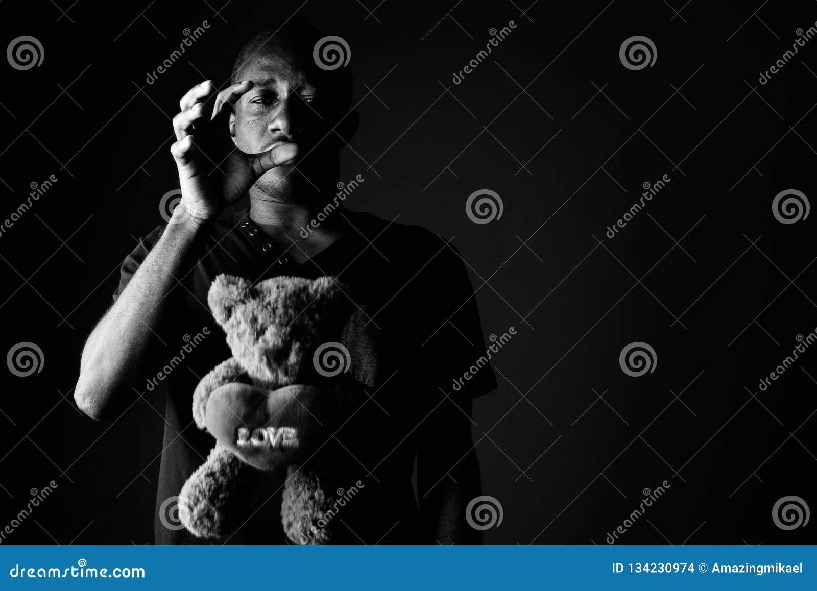 Homem africano novo deprimido triste com urso de peluche e texto do sinal do amor em preto e branco