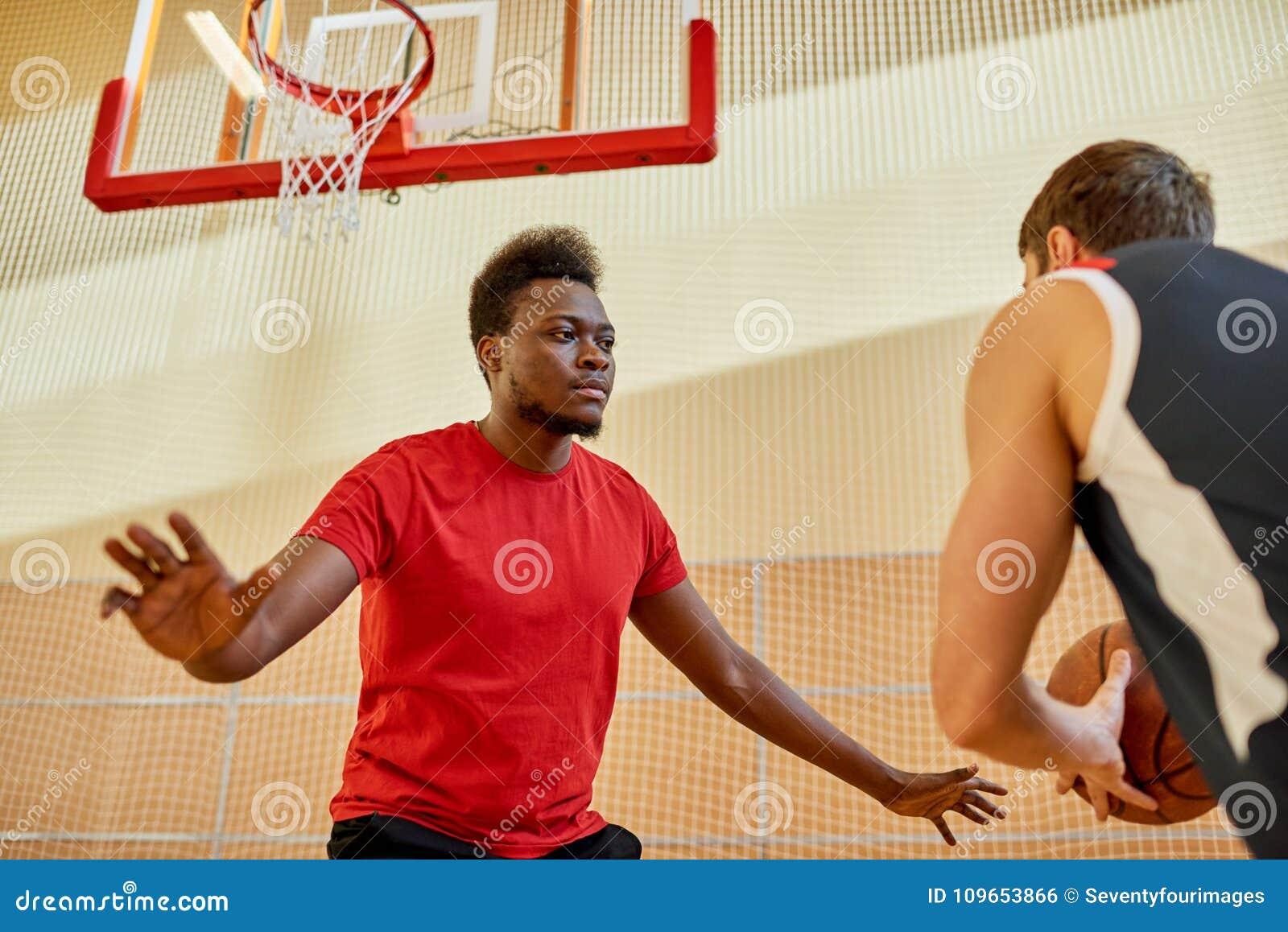 Homem africano que joga a defesa no basquetebol