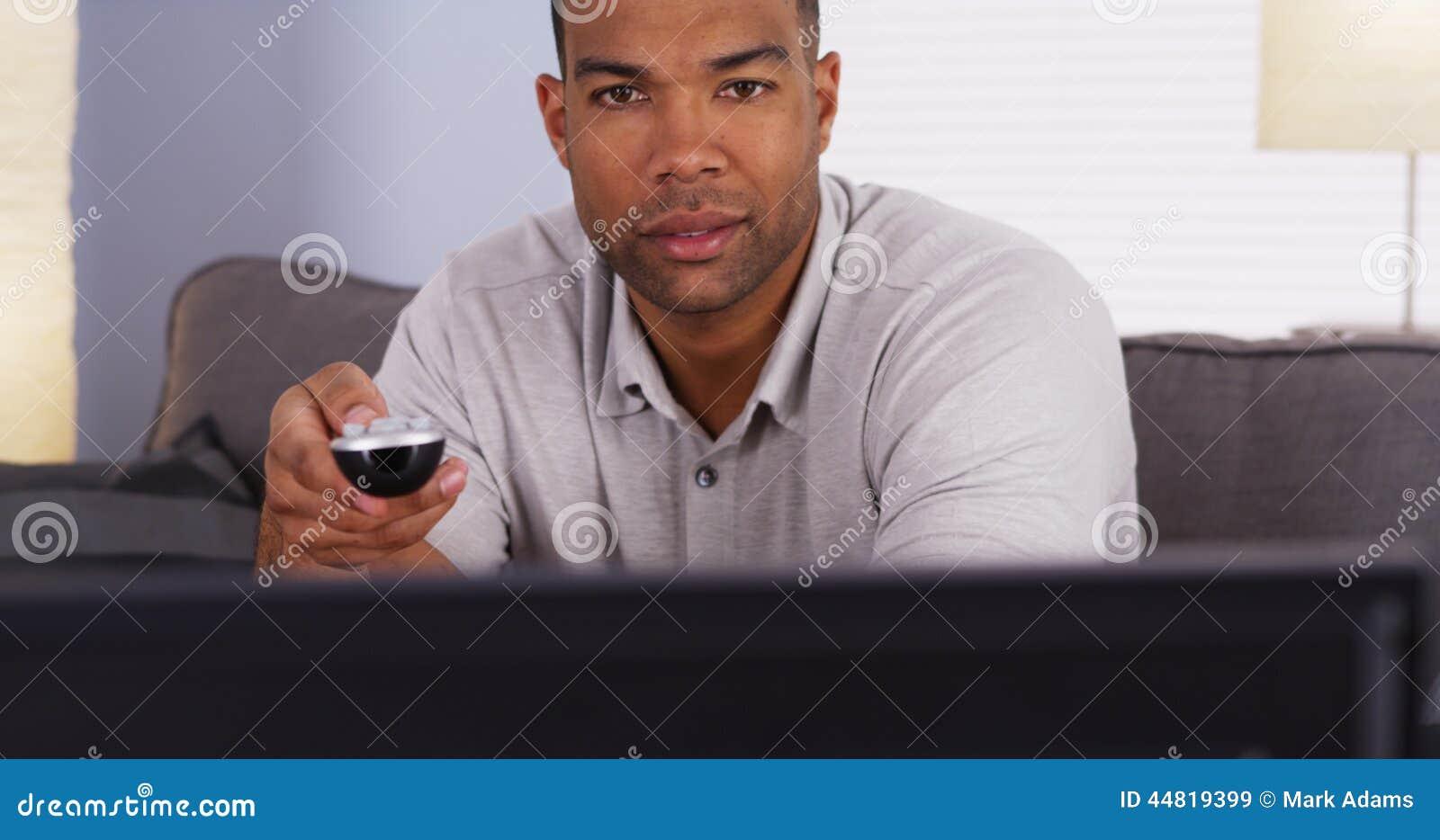 Homem africano que lança através dos canais na tevê