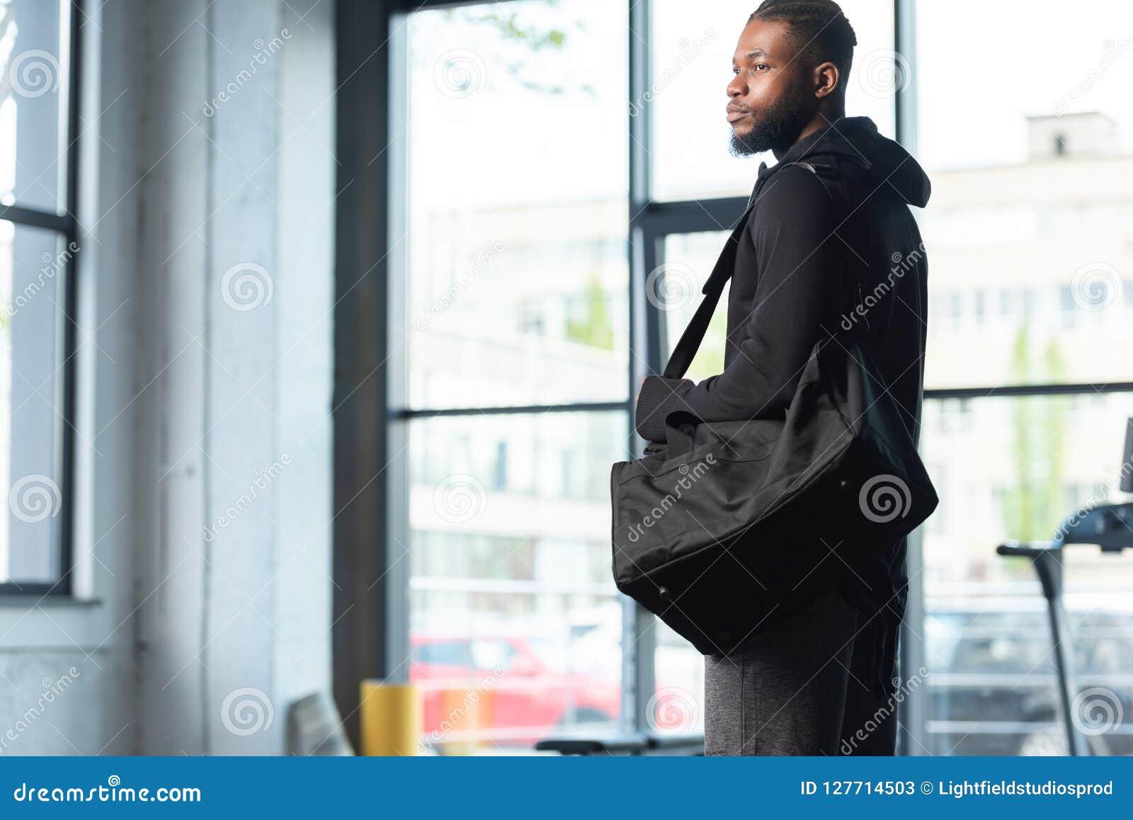 Homem afro-americano considerável no saco e na vista da terra arrendada do sportswear afastado