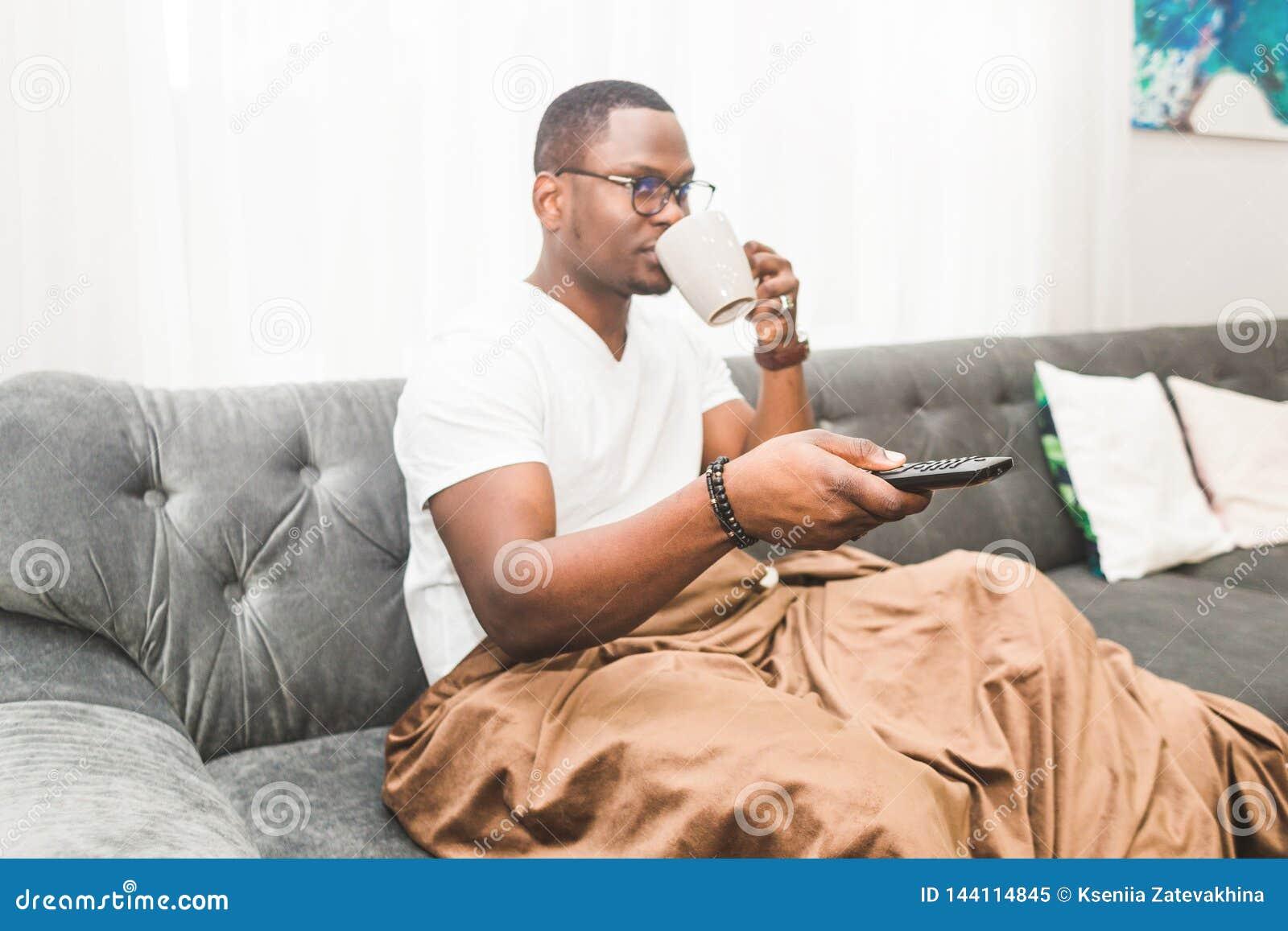 Homem afro-americano novo, coberto com uma cobertura, tevê de observação em casa
