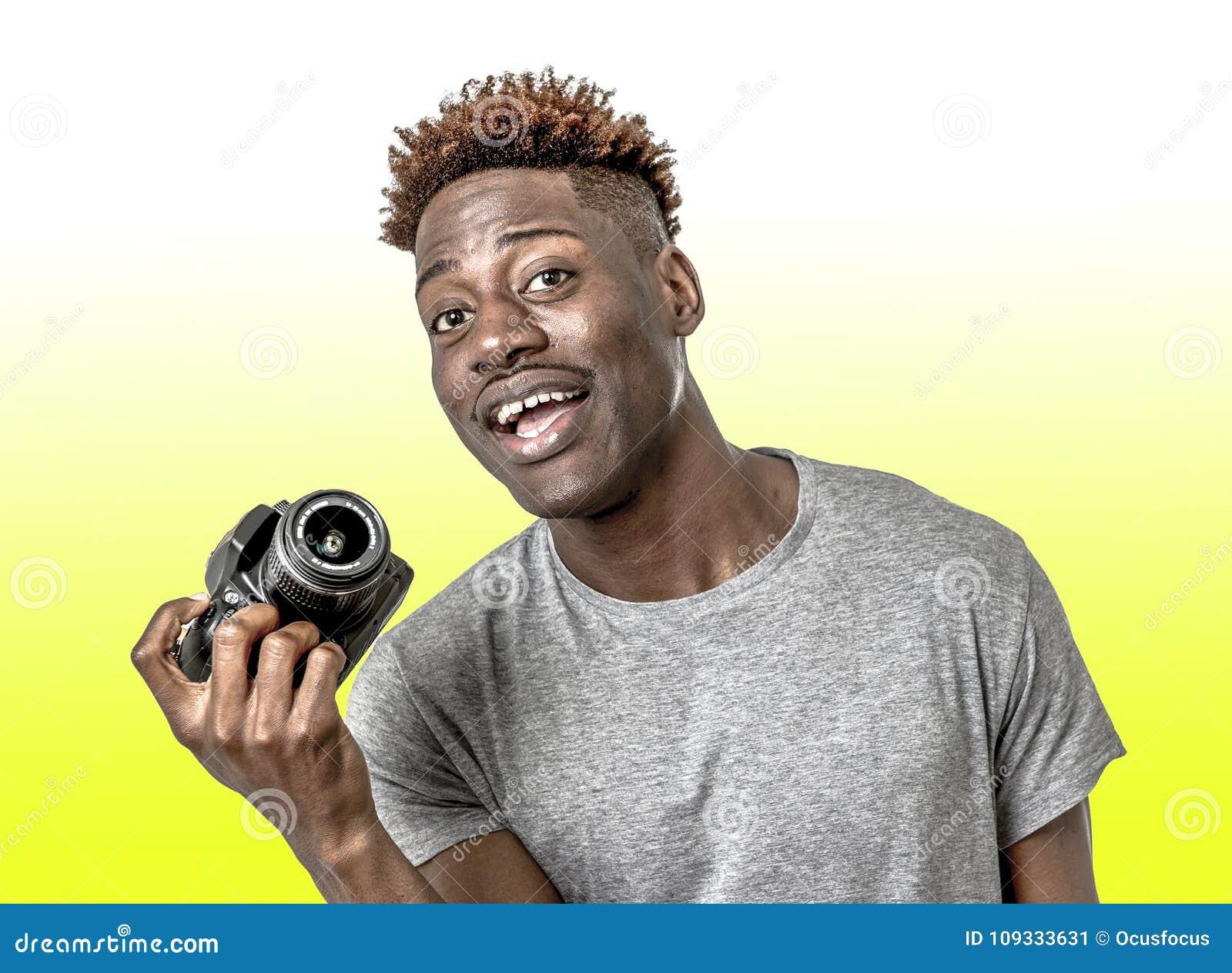 Homem afro-americano preto feliz atrativo e fresco novo que mantém entusiasmado de sorriso da câmera reflexo digital da foto isol