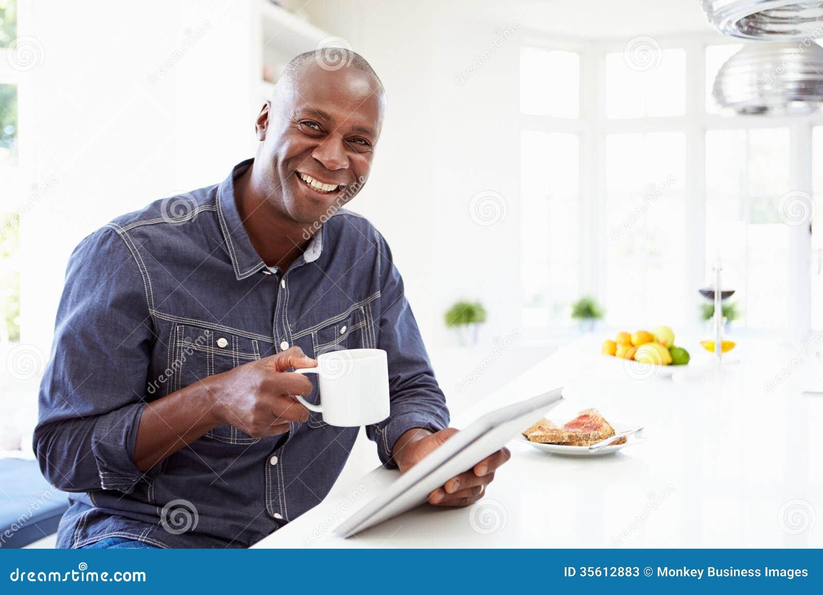 Homem afro-americano que usa a tabuleta de Digitas em casa