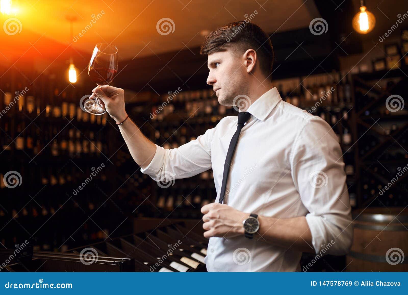 Homem agradável novo que identifica e que discute vinhos