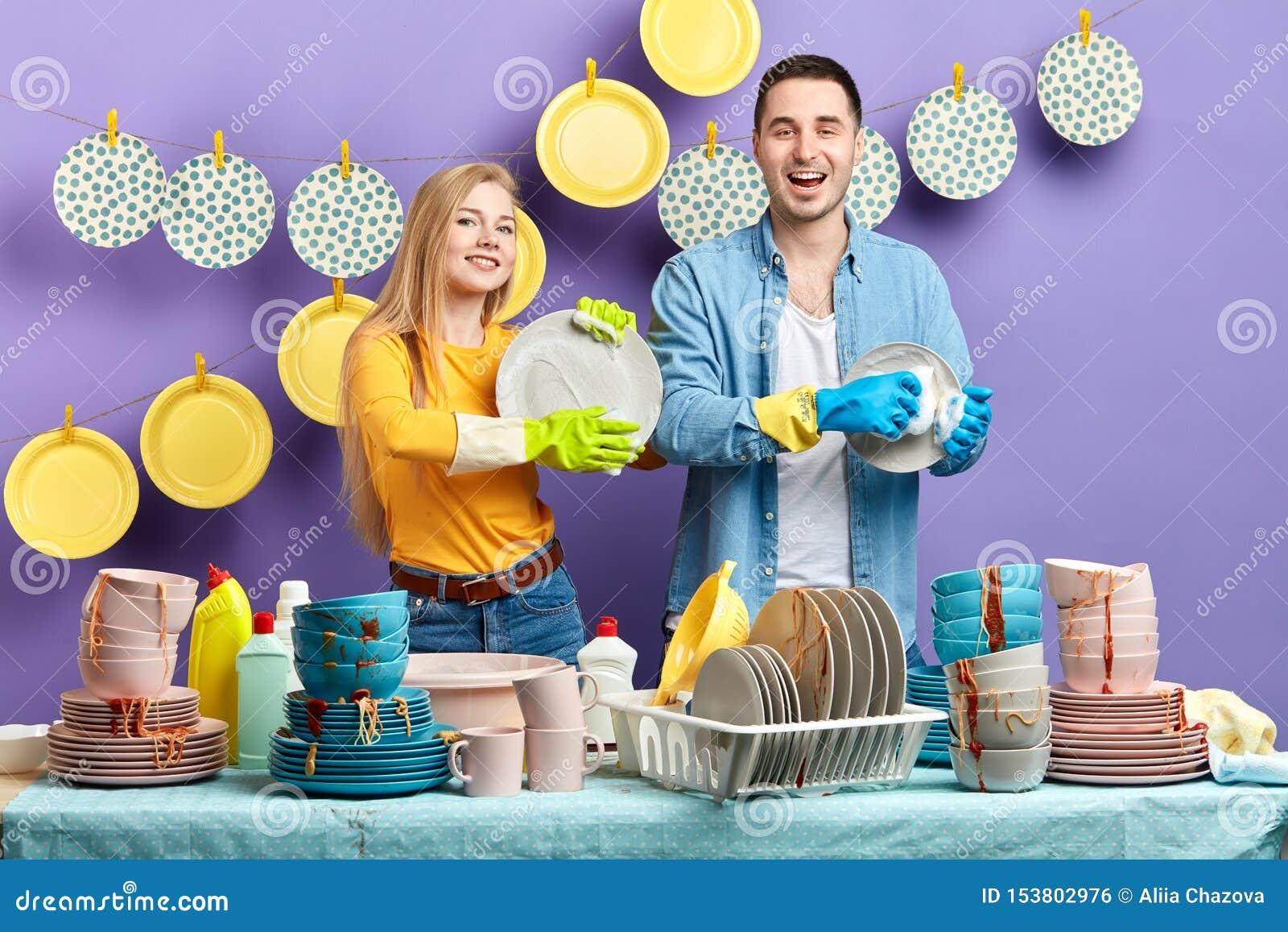 Homem alegre e mulher agradáveis que lavam as placas após o partido