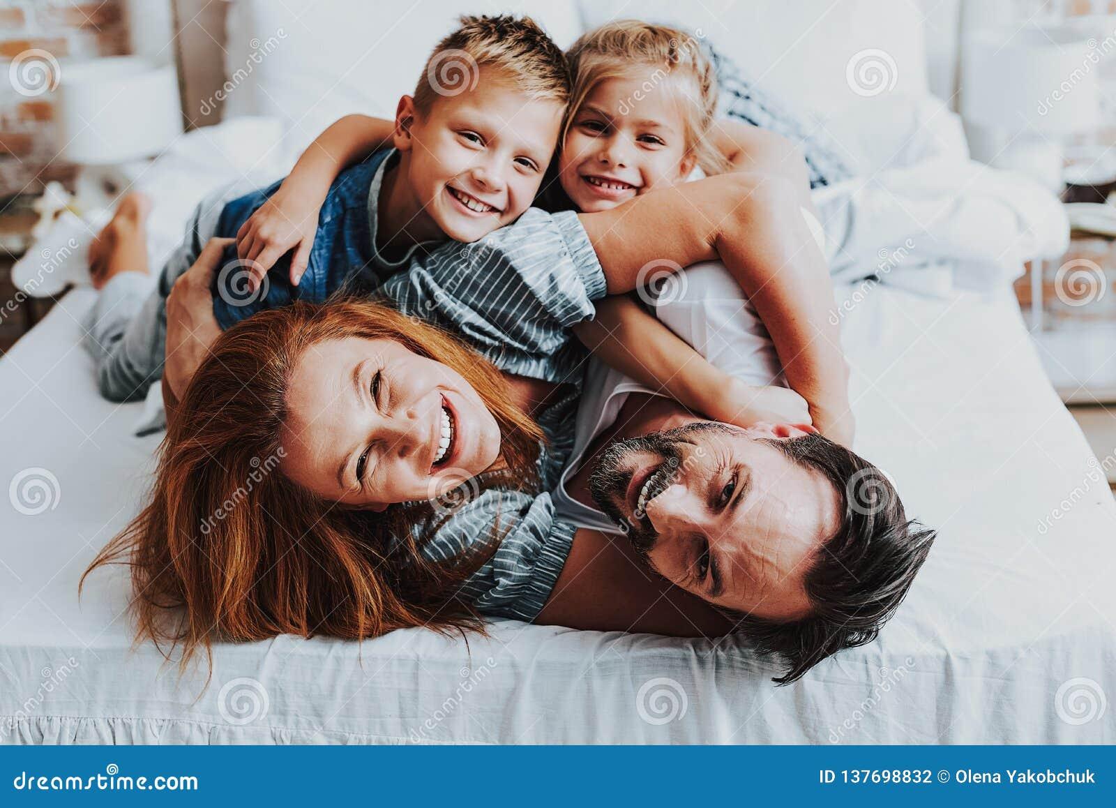 Homem alegre e mulher que jogam com crianças
