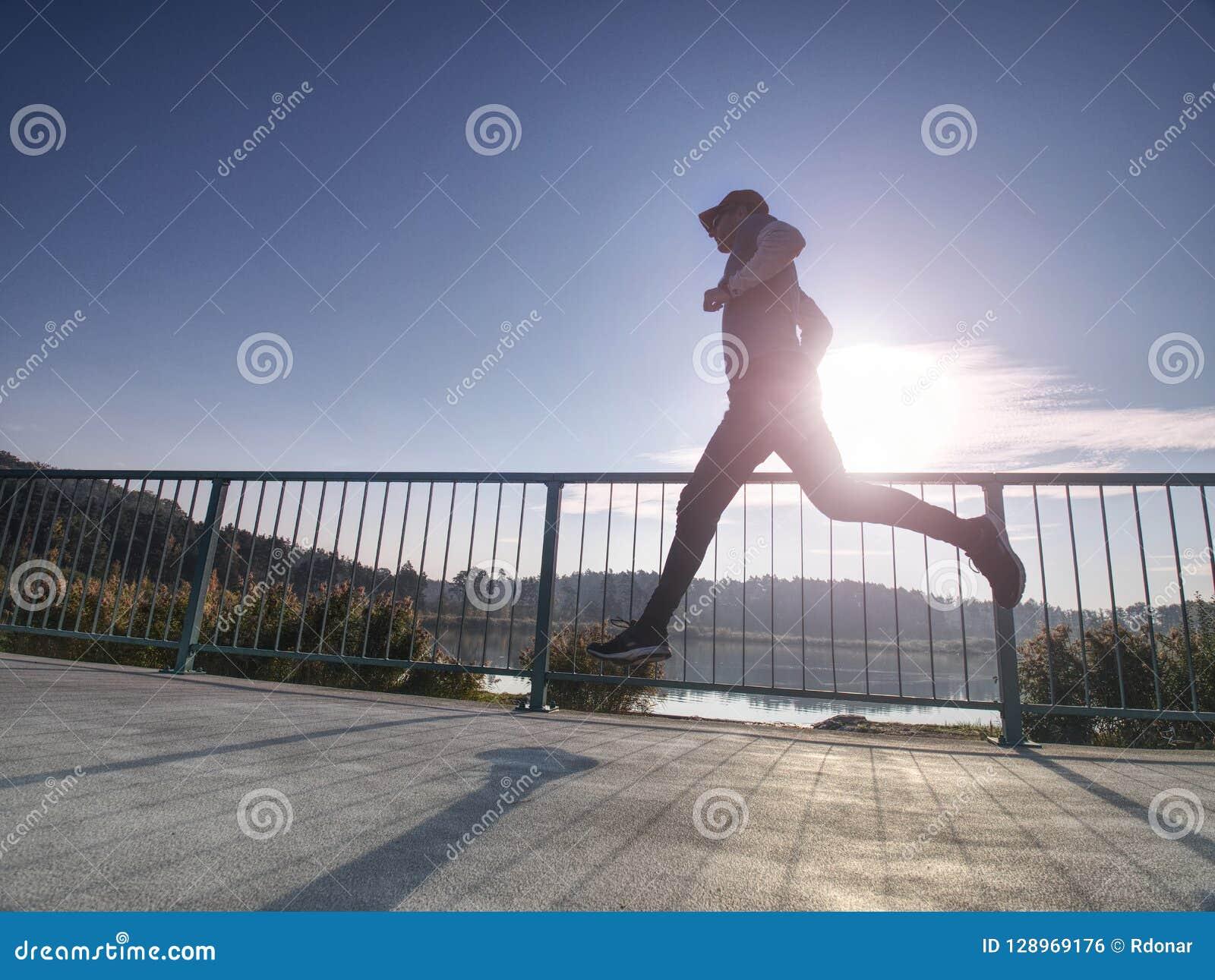 Homem alto com óculos de sol, o boné de beisebol vermelho e o sportswear preto azul