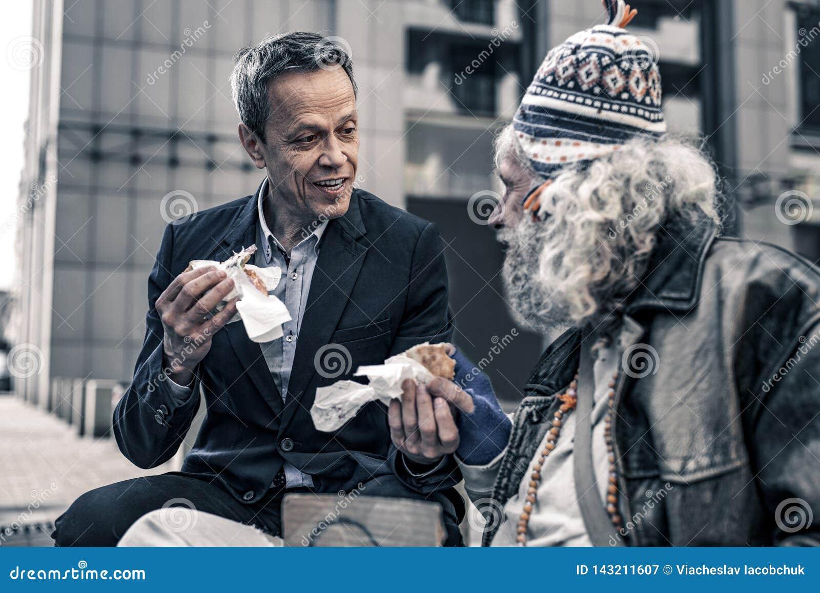 Homem amável comunicativo que fala aos sem abrigo superiores cinzento-de cabelo