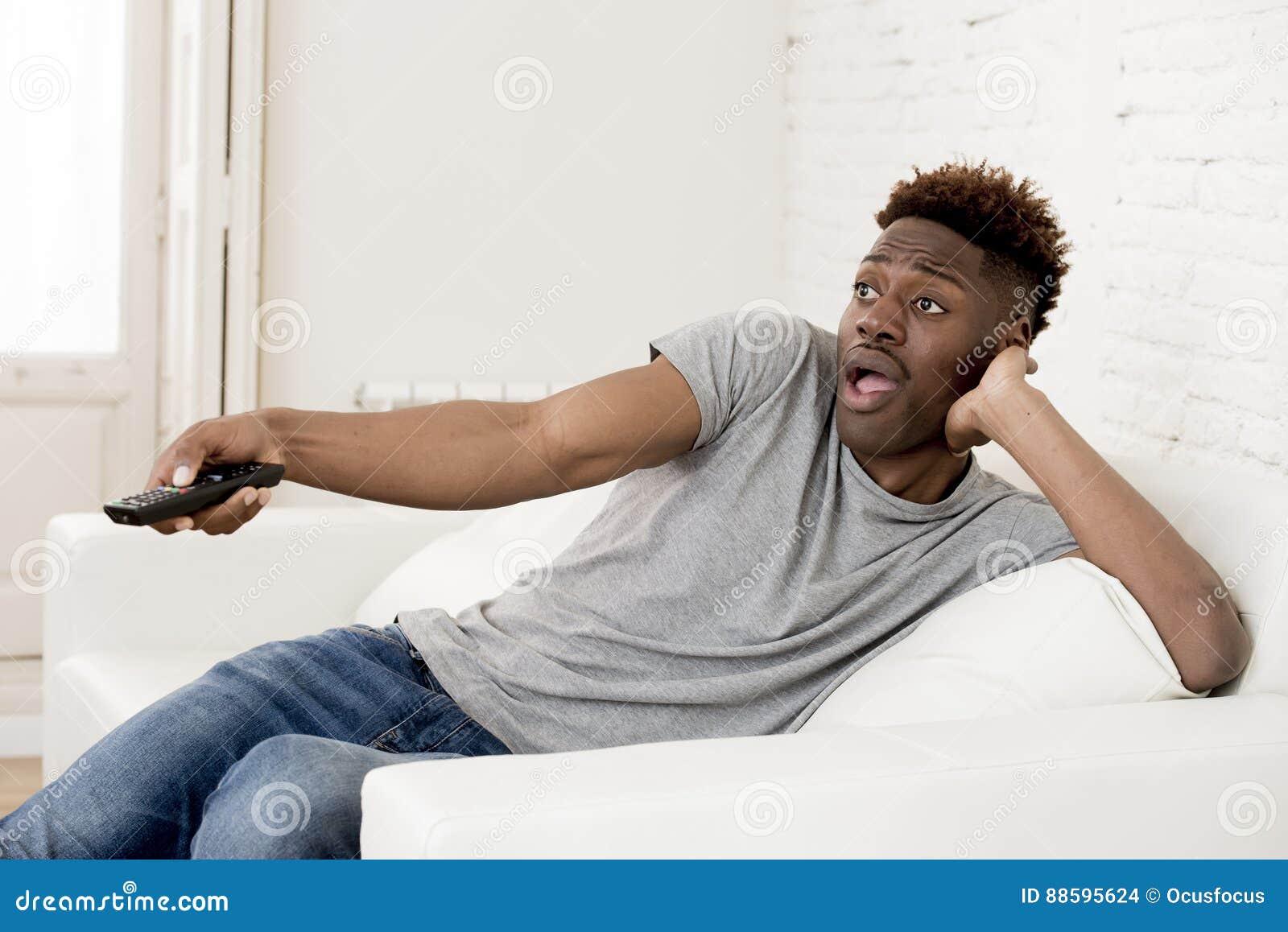 Homem americano do africano negro atrativo que senta em casa a televisão de observação do sofá do sofá