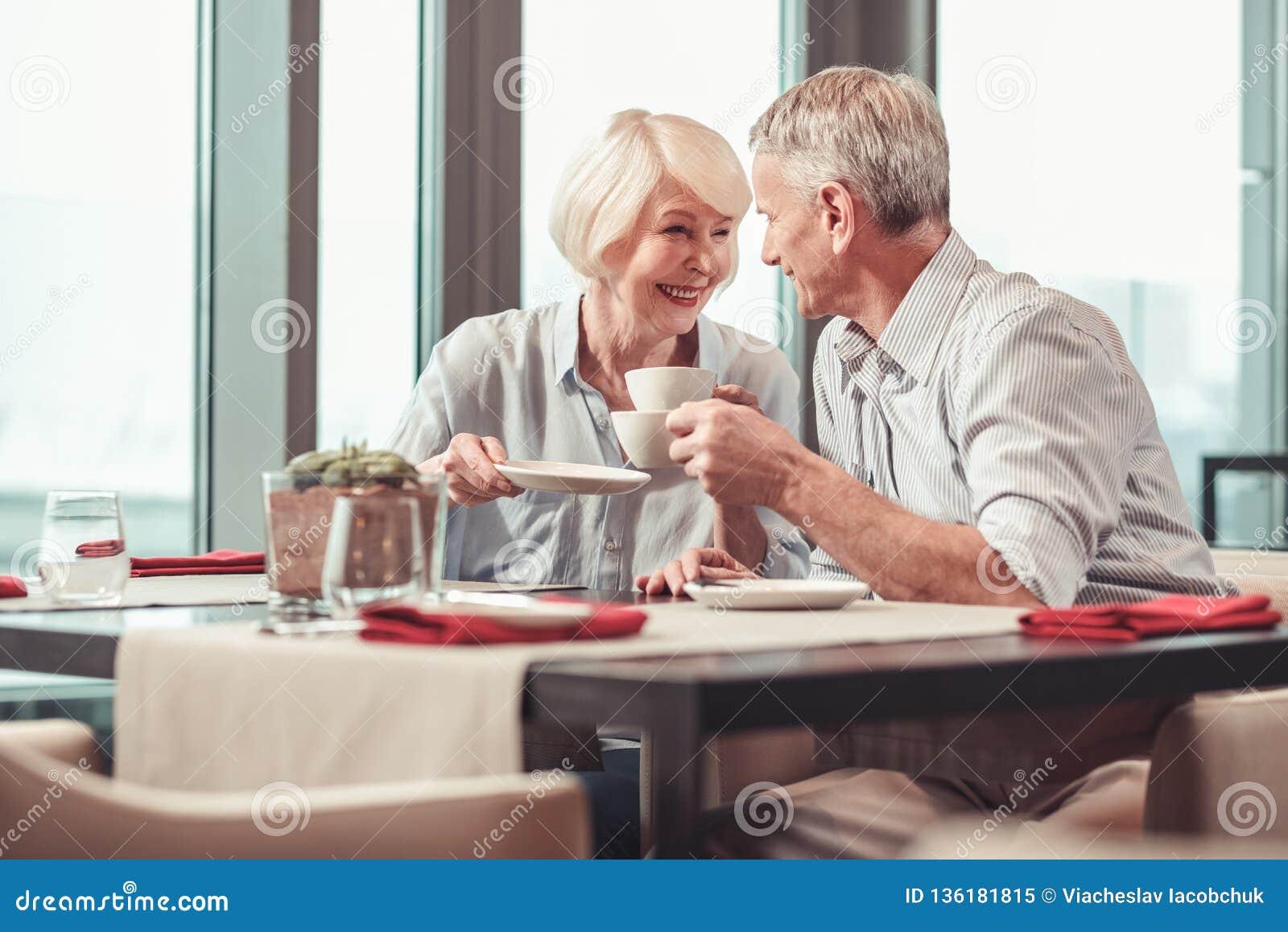Homem aposentado e mulher que comem o café da manhã junto
