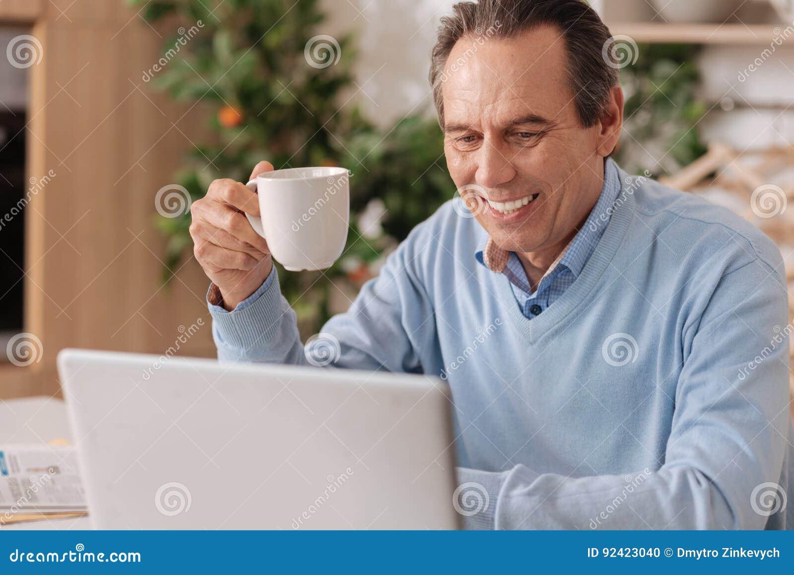 Homem aposentado feliz que usa o dispositivo eletrônico em casa