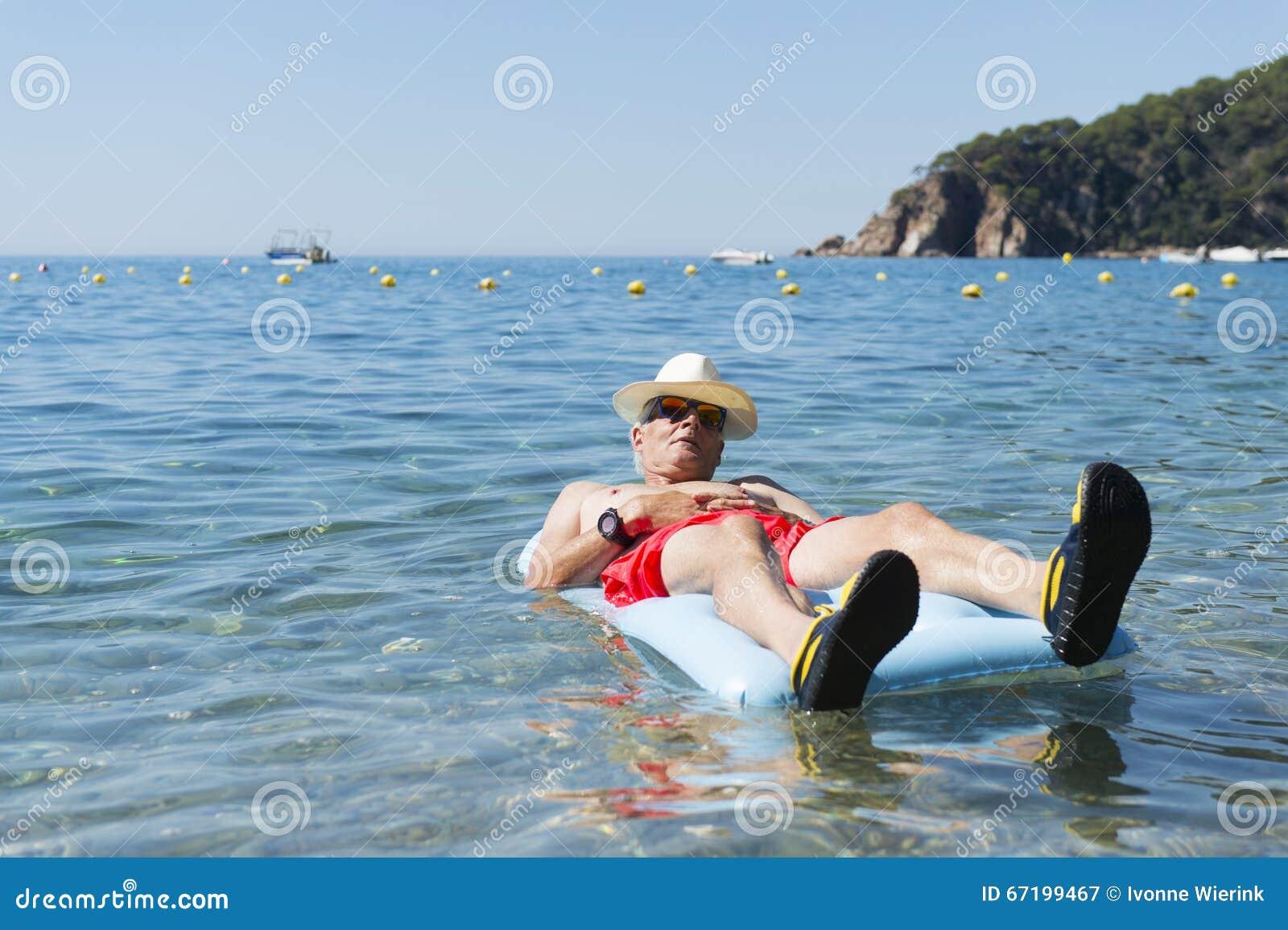 Homem aposentado que joga na água do mar
