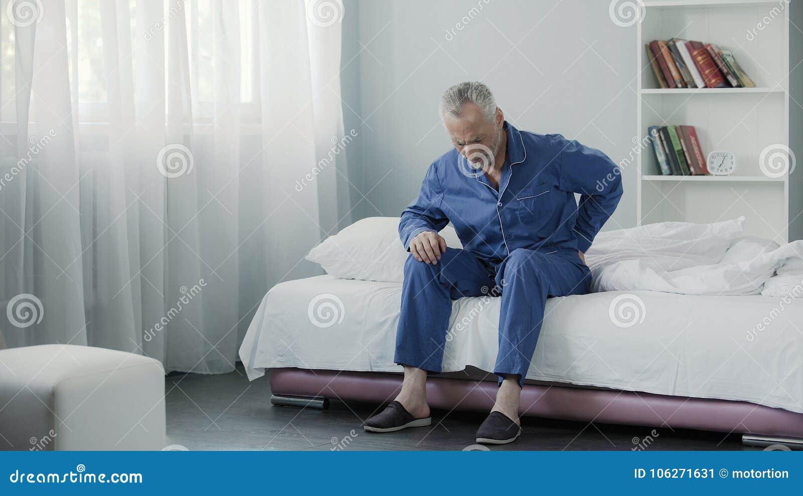 Homem aposentado que senta-se na cama e parte traseira, saúde e doença terríveis de sentimento da dor dentro
