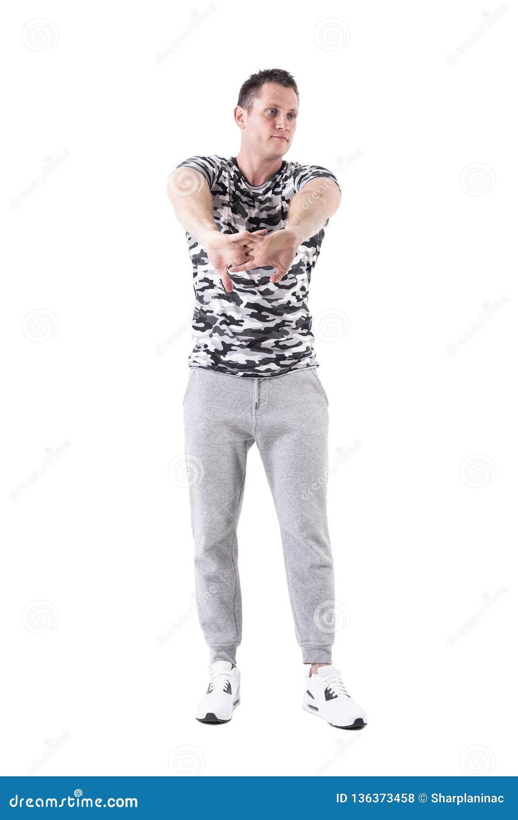 Homem apto atlético do esporte que estica os braços que aquecem-se e que preparam-se para o exercício