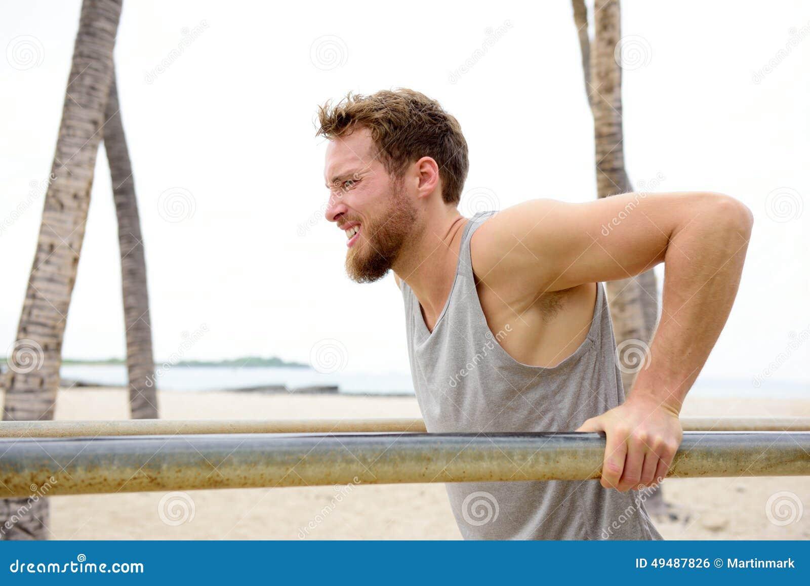 Homem apto da cruz que dá certo fazendo exercícios dos mergulhos